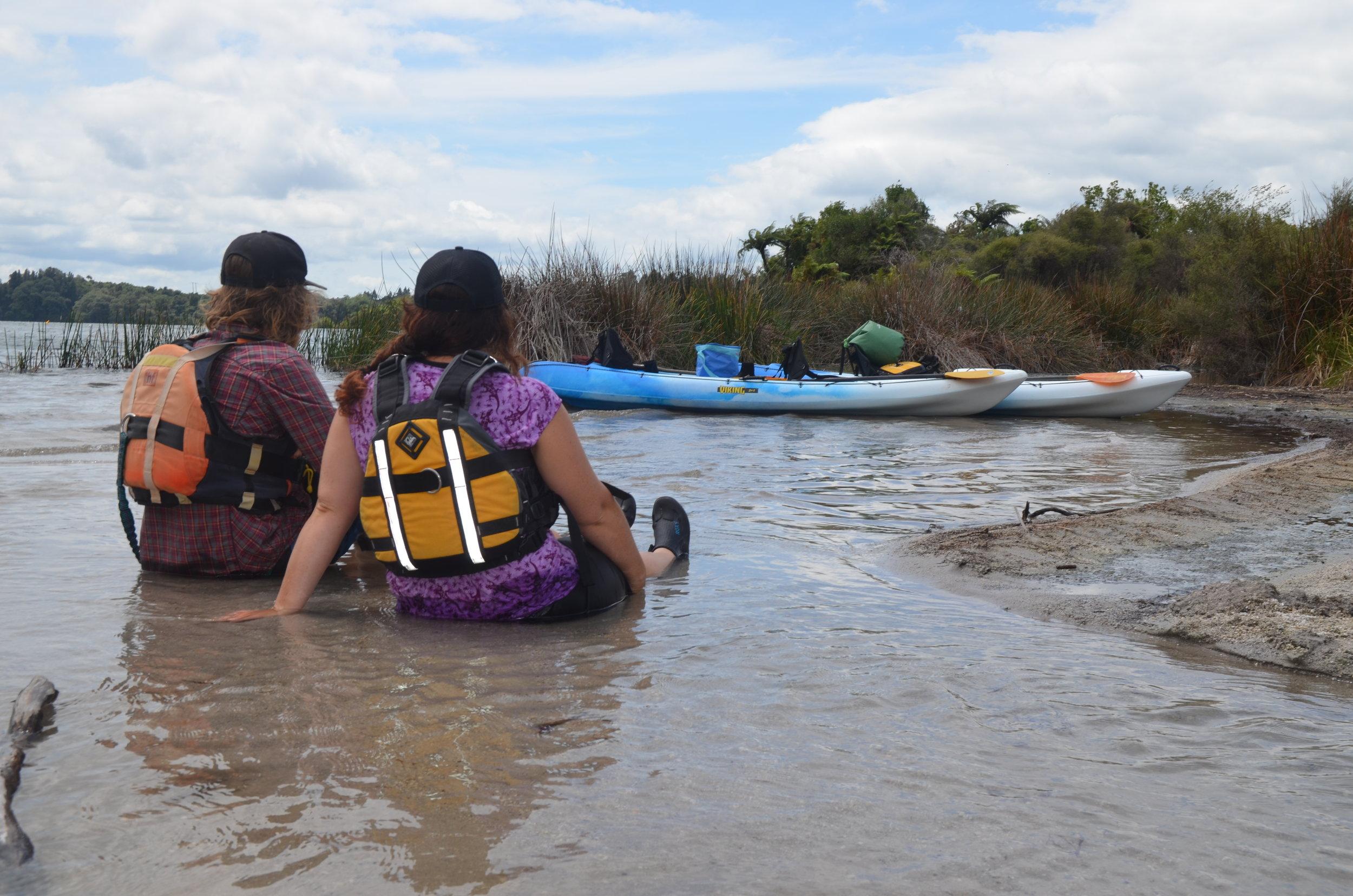 Two people in hot pools plus kayaks in background.JPG