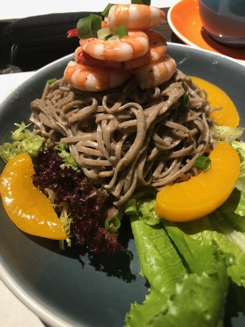 Chilled soba noodles in a sesame sauce, peaches, shrimp, and lettuce in a salted vinaigrette sauce, garnished with fresh green onions.