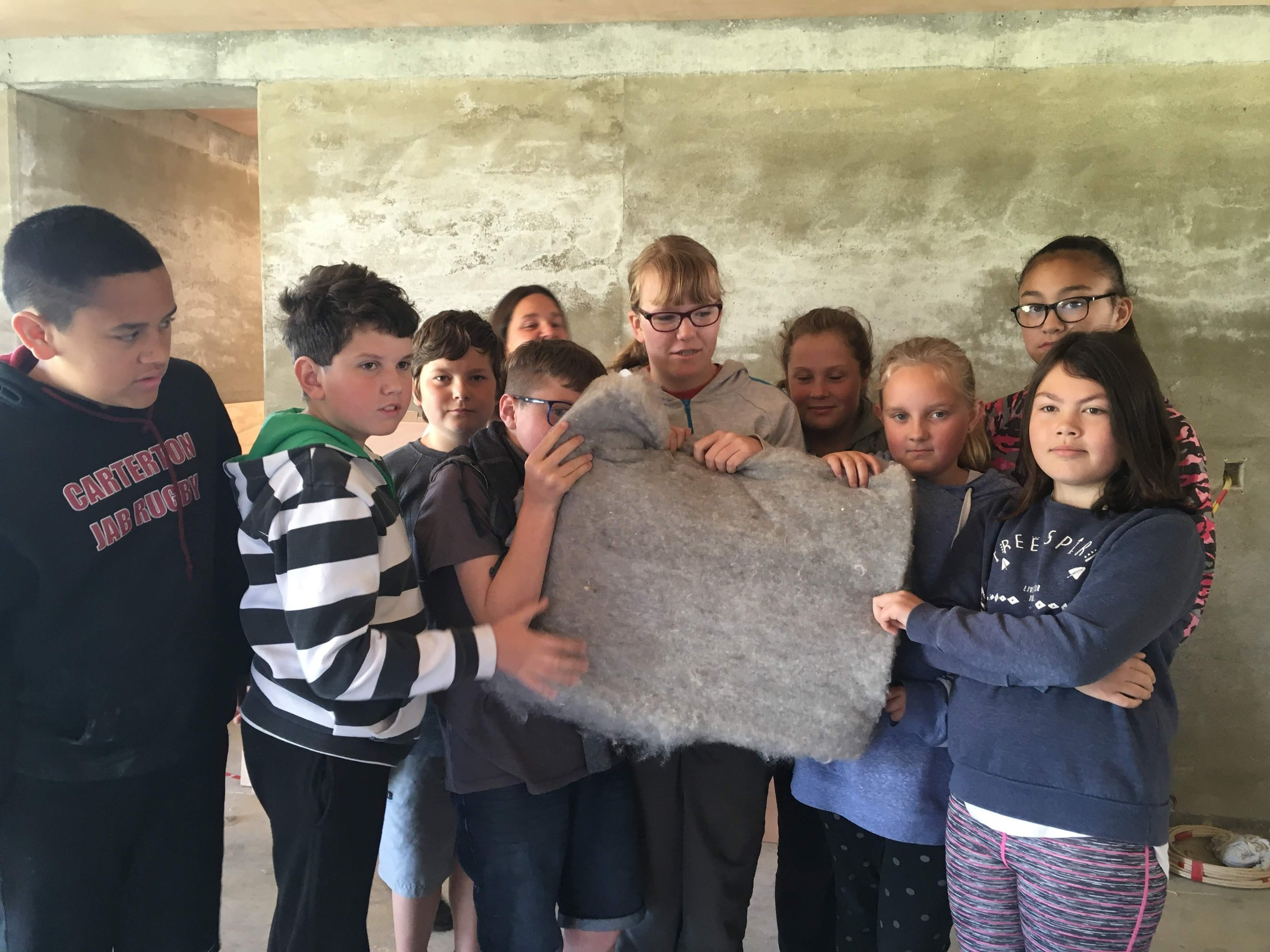 Students from South End School Carterton investigate insulation options - here is wool insulation in a rammed earth house building site in Carterton