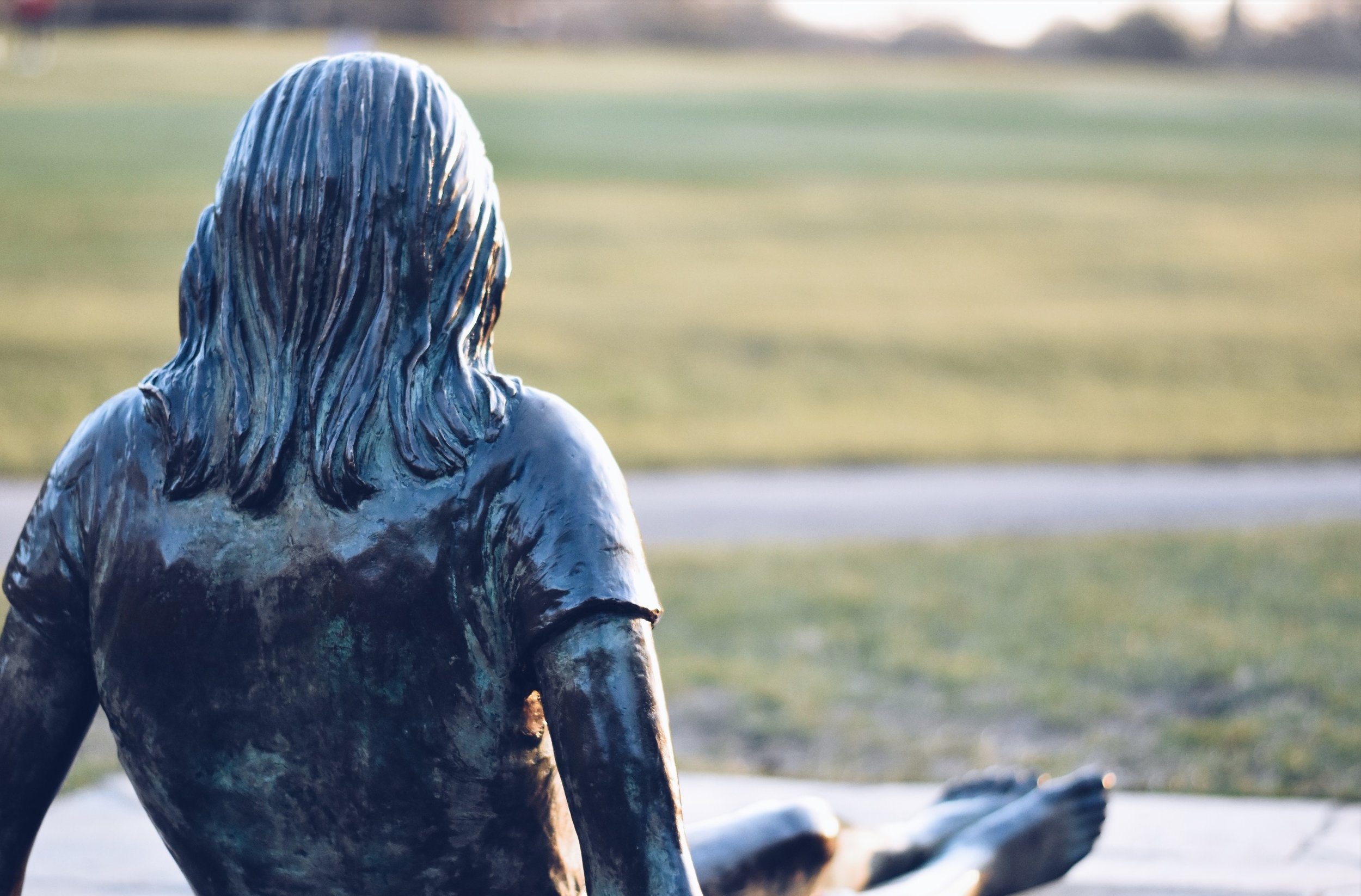 This young woman, flip flops beside her, has been relaxing in the park for nearly thirty years. She looks a bit chilly in winter.