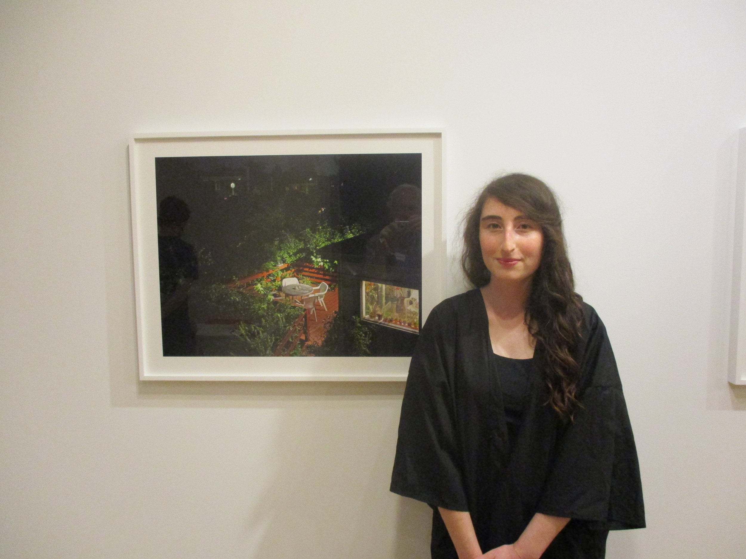 """Sarah Meulhbauer at the opening of the show at Happylucky no. 1 gallery called """"To Find Home."""" The Sarah Lawence graduate is standing next to a photo of her parents house in Queens. Three other artists participated in the show."""