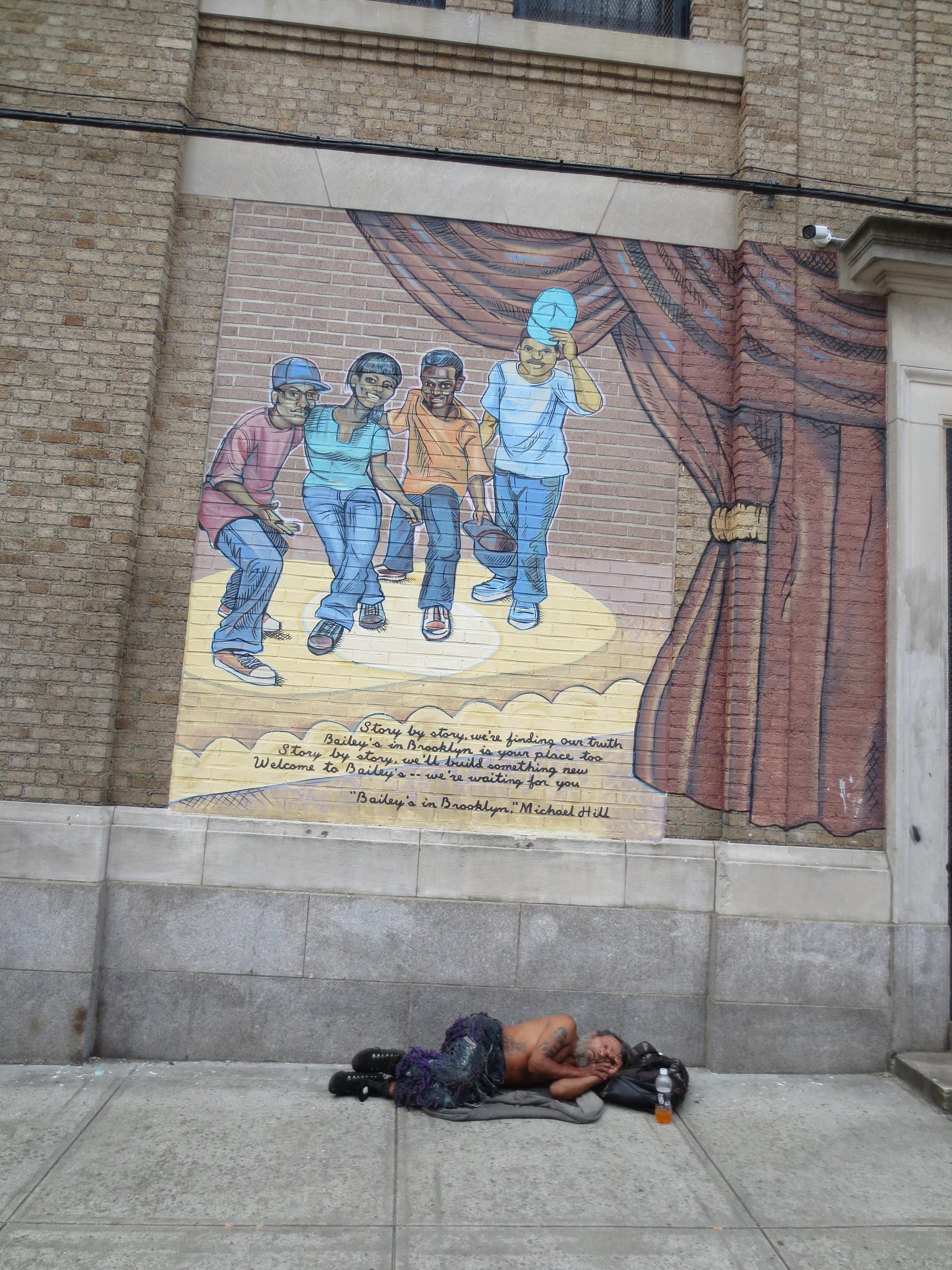 Man sleeping under Black History mural Herkimer Street