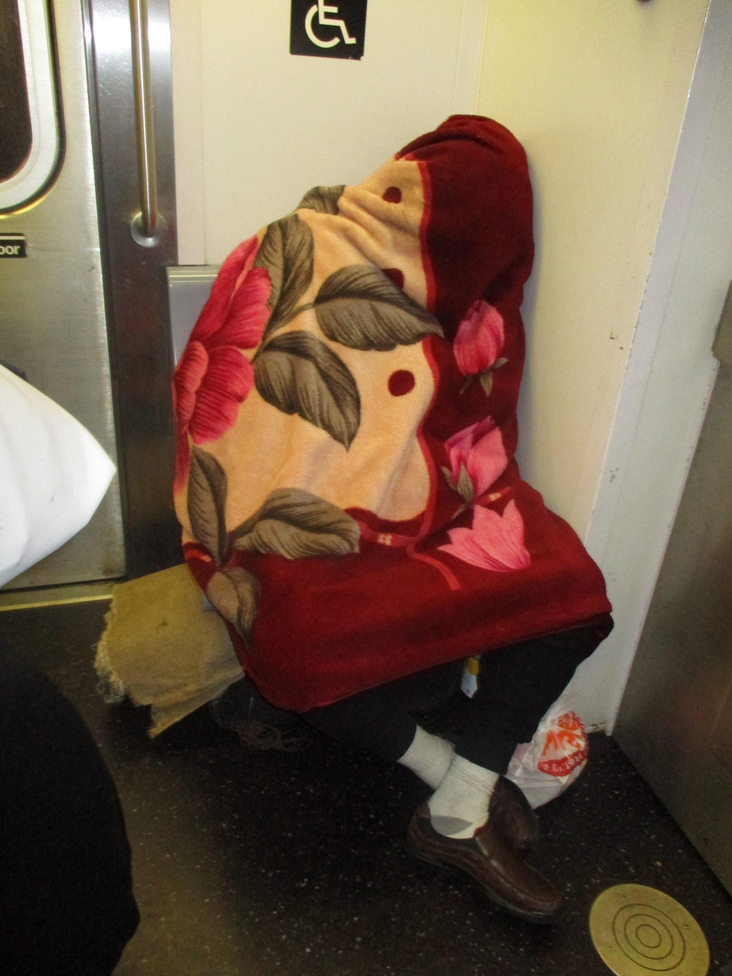 Man on the train trying to sleep.