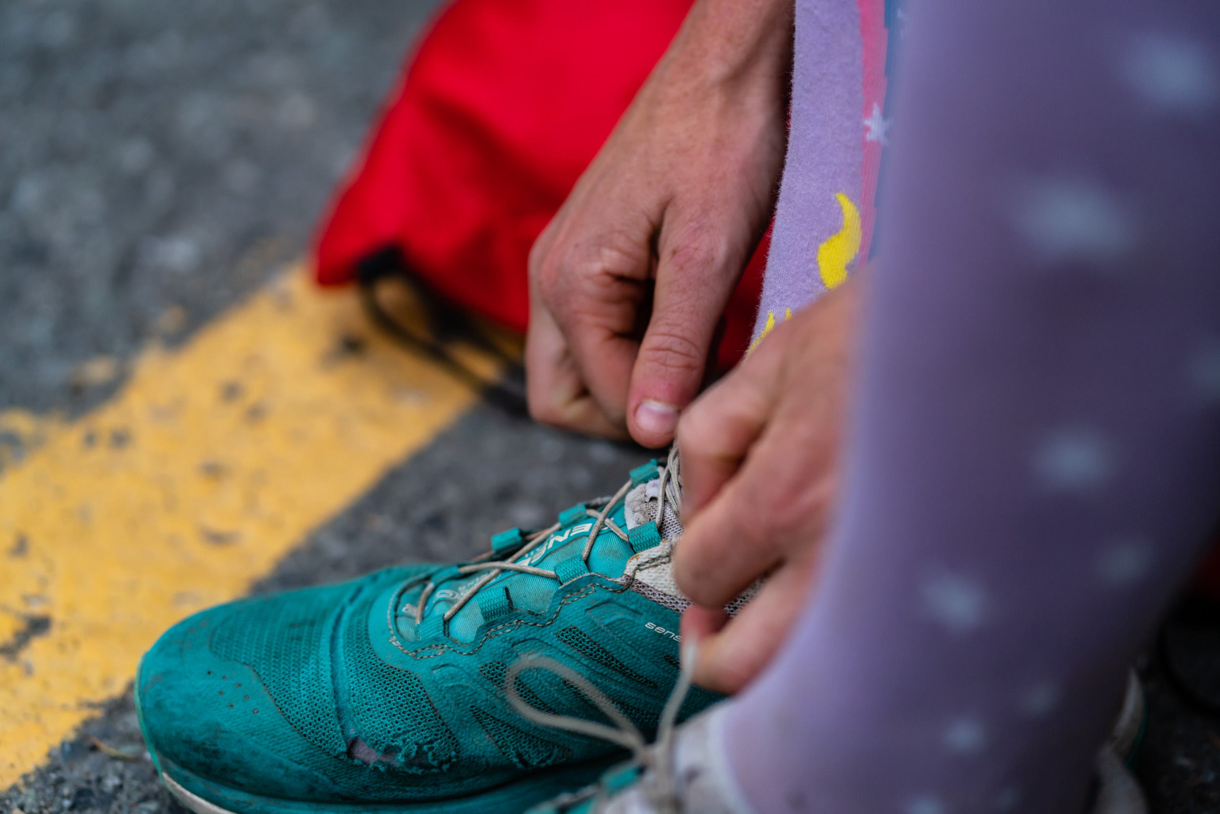 Alicia Woodside tying her shoes as she gets ready to go for a trail run, Squamish, British Columbia