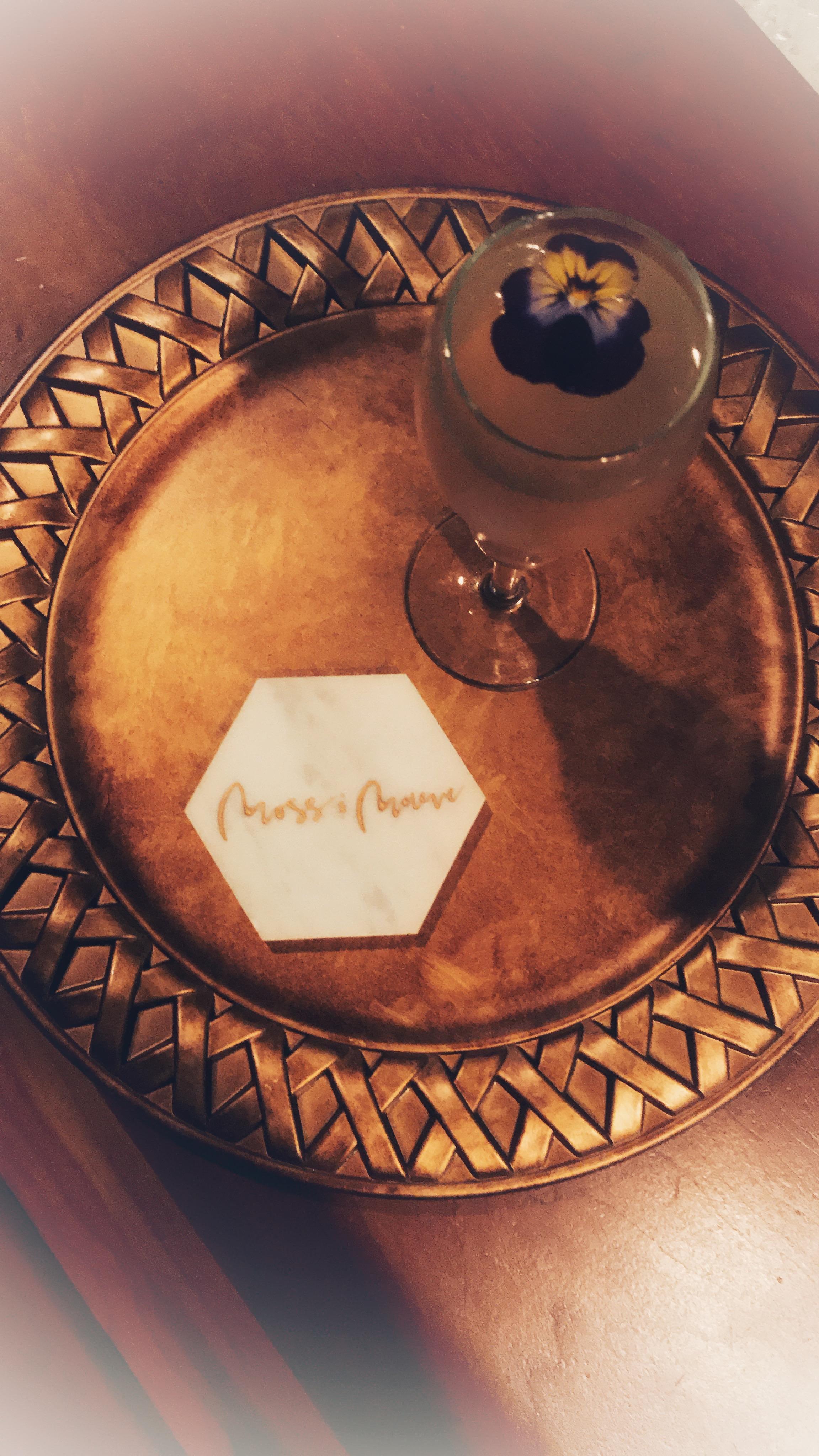 - Leopoldo Silver Tree Vodka (1 oz)Lemon JuiceSimple SyrupCreme de Rose Liqueur (1/2 oz)ChampagneKavaViola Flower