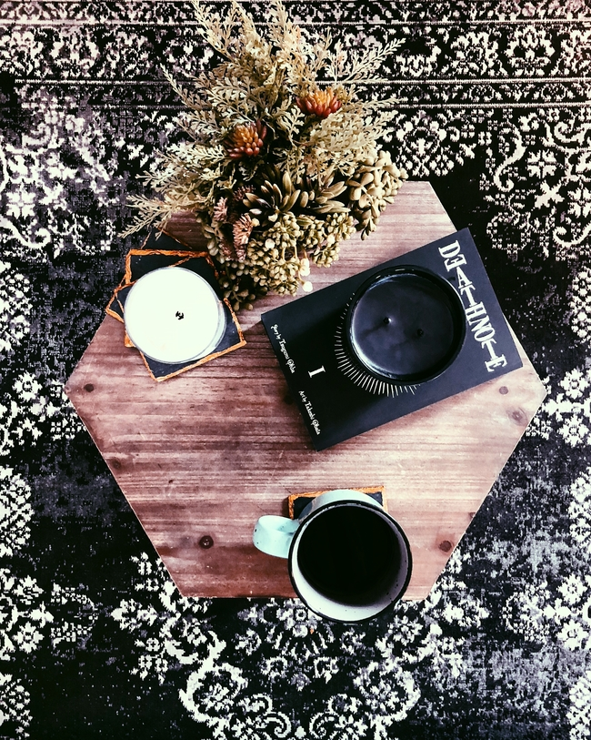 Rustic coffee table decor styled with Death Note manga and faux greenery over a vintage style rug.