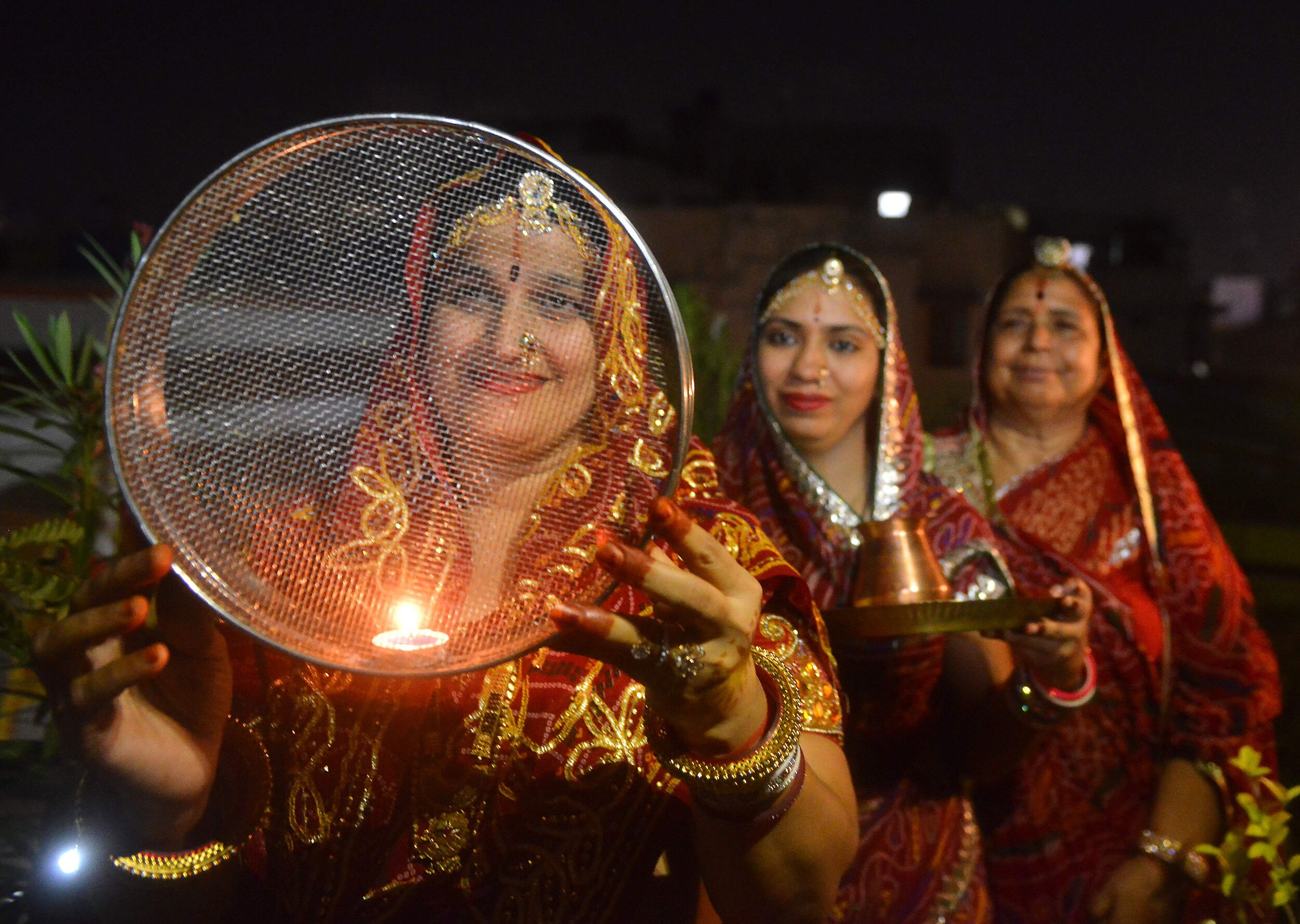Women dressed in wedding reds for karvachauth. Image Credits:  Unrealistic Trends Blog