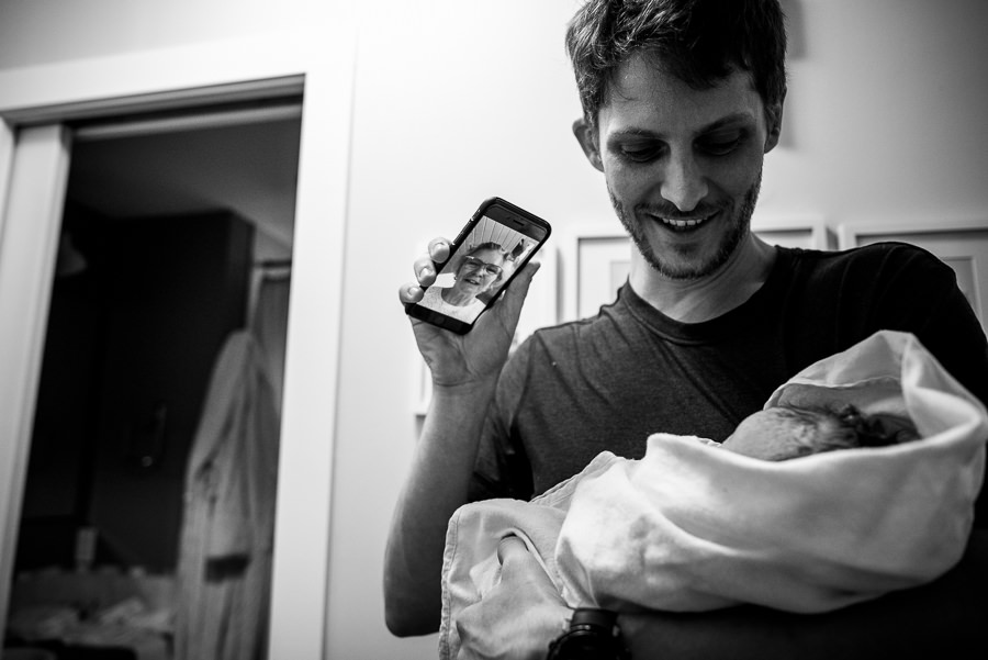 dad talking to mother in law on phone to share news of baby girl