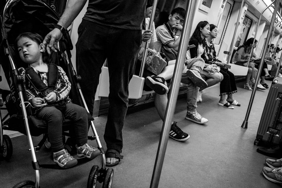 girl riding a train with her parents