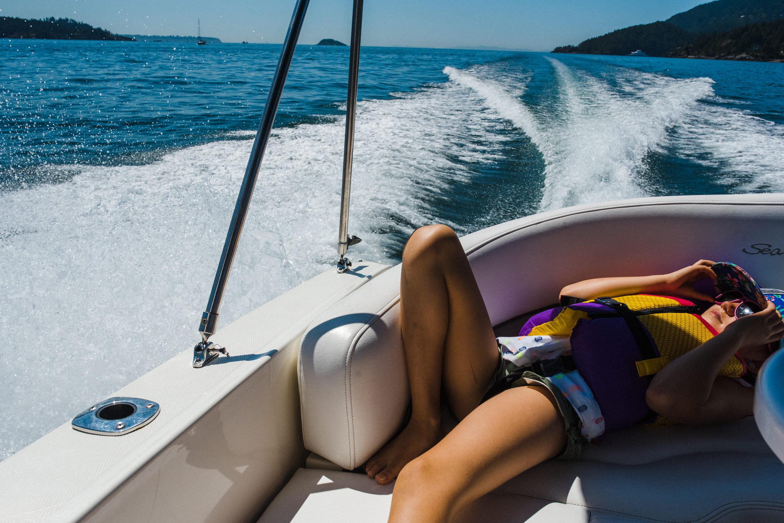 girl enjoying the sun and splash while lying on the boat seat