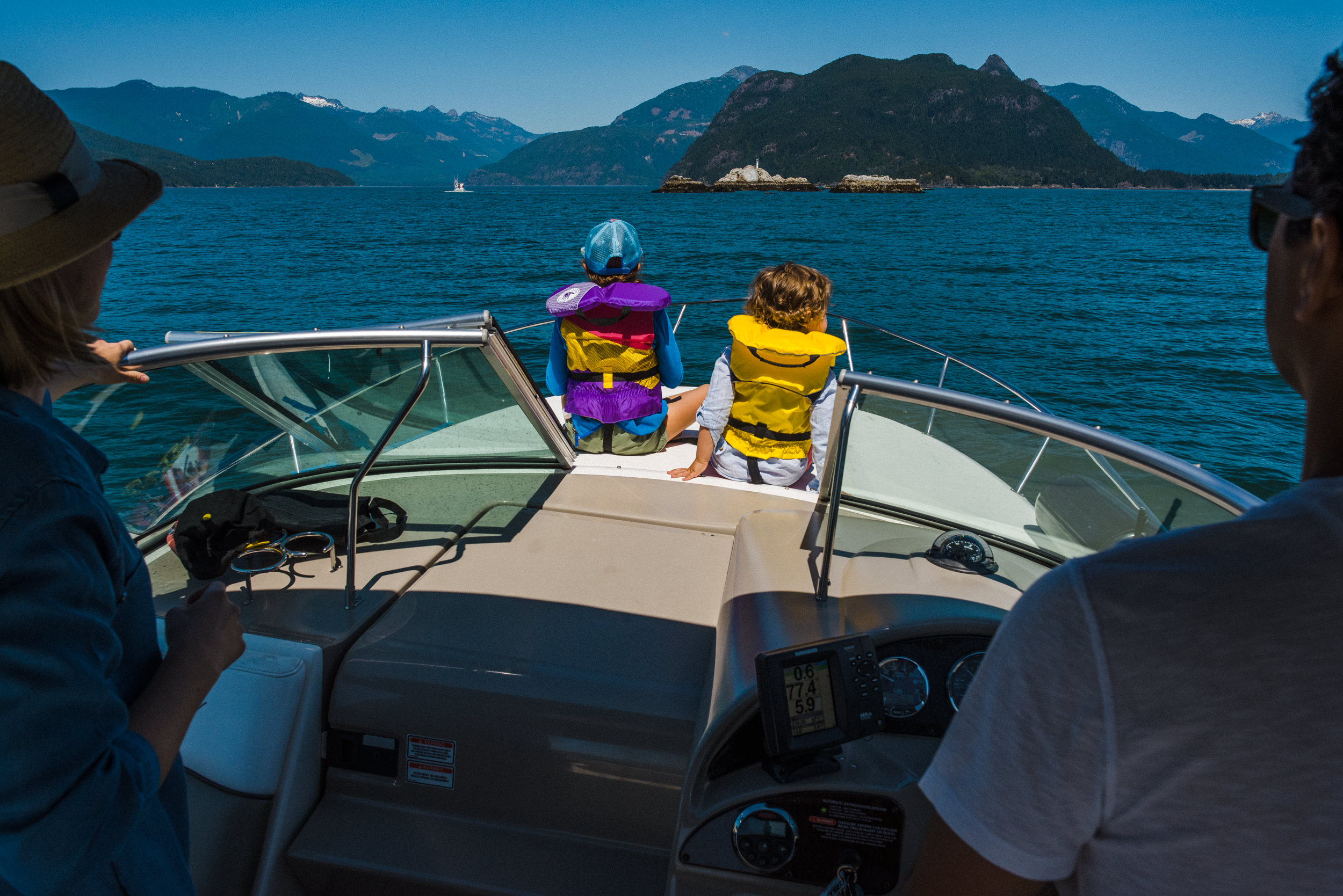 family of four boating towards anvil island in howe sound