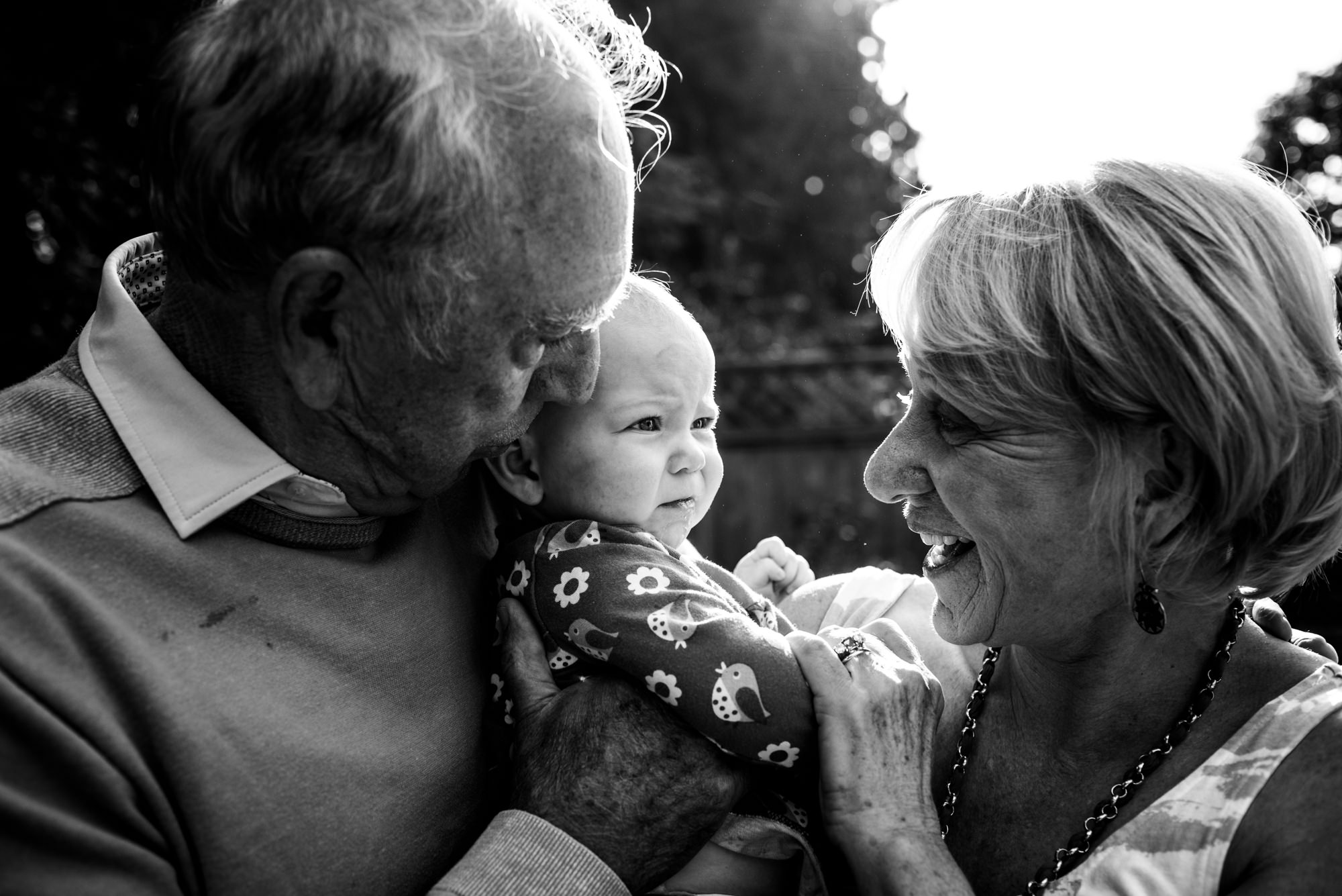 grandparents smile while hugging their newest baby granddaughter