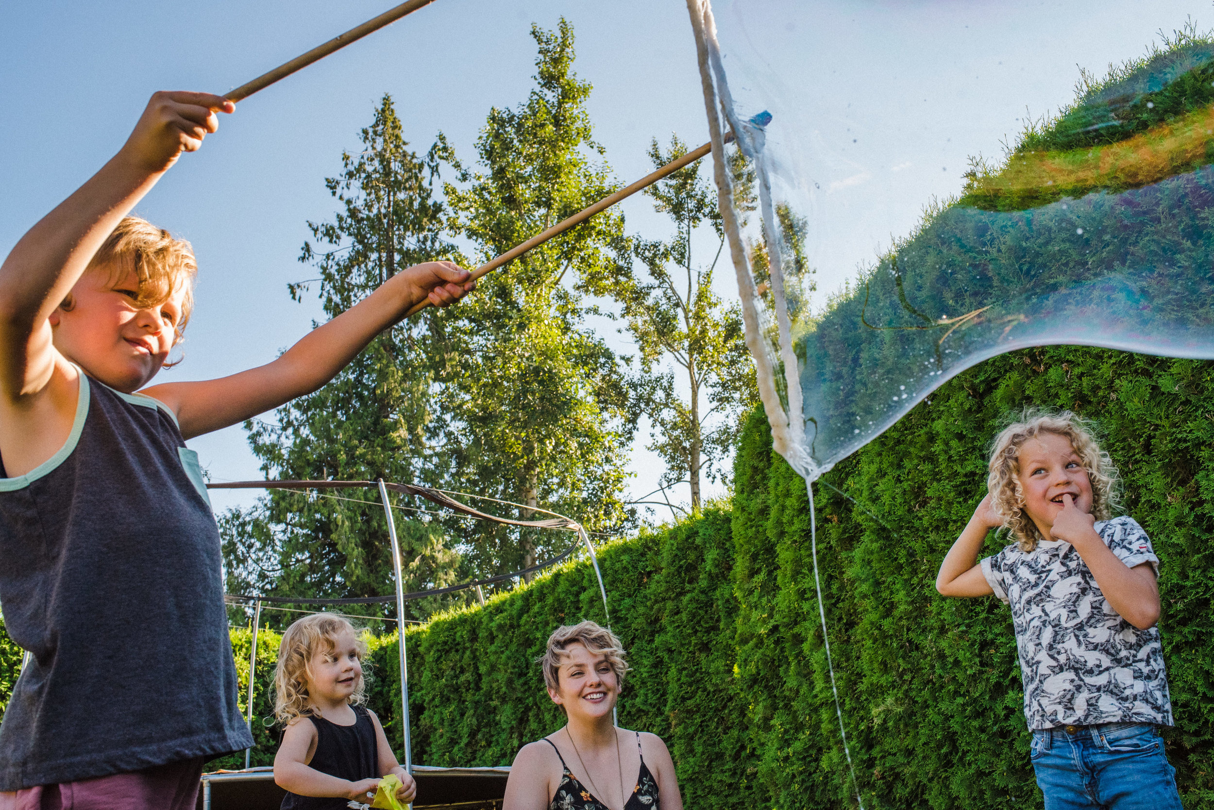 Three siblings trying to make big bubbles with rope and rods while their mom looks on smiling.