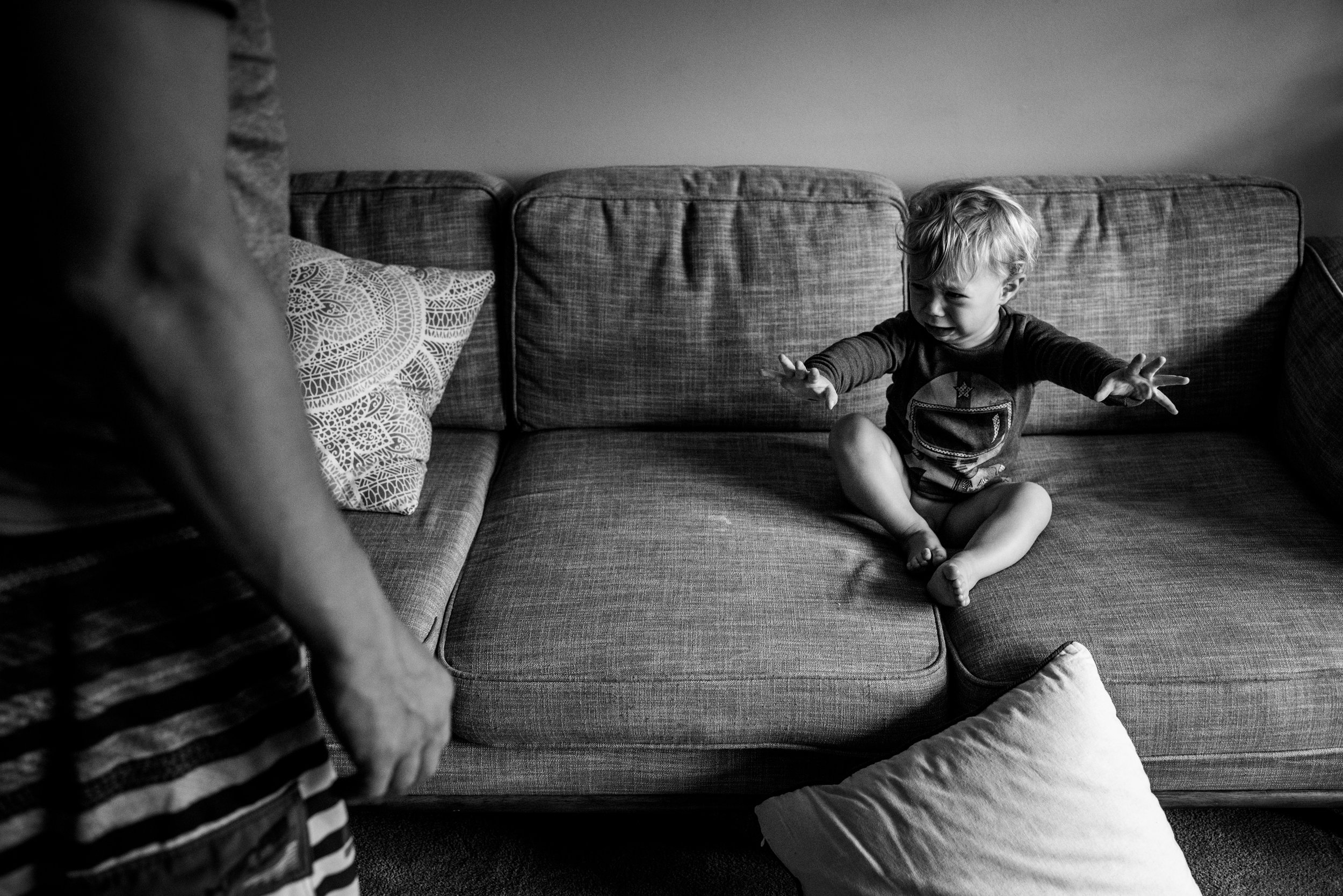 Toddler boy sitting on the couch and unhappy about getting dressed.
