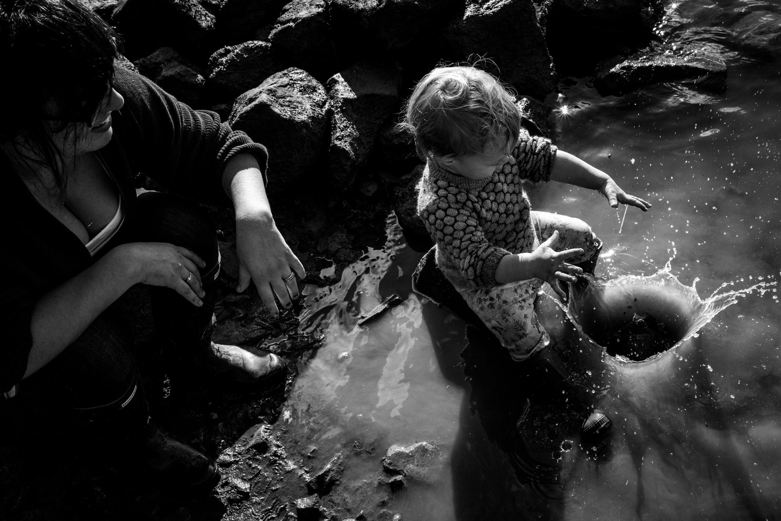 Toddler boy throwing big rocks into river water, making big splashes.