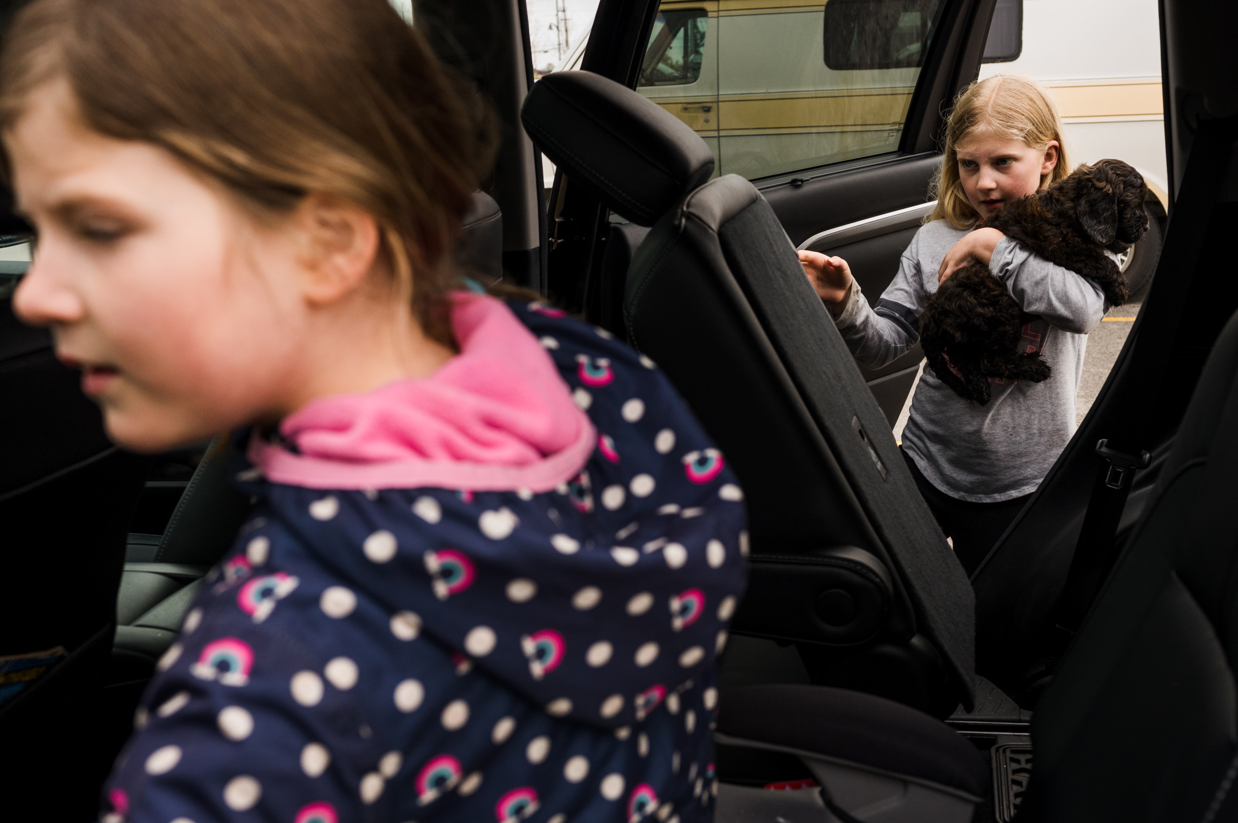 a girl carrying her new puppy into the car while her younger sister gets into her car seat.