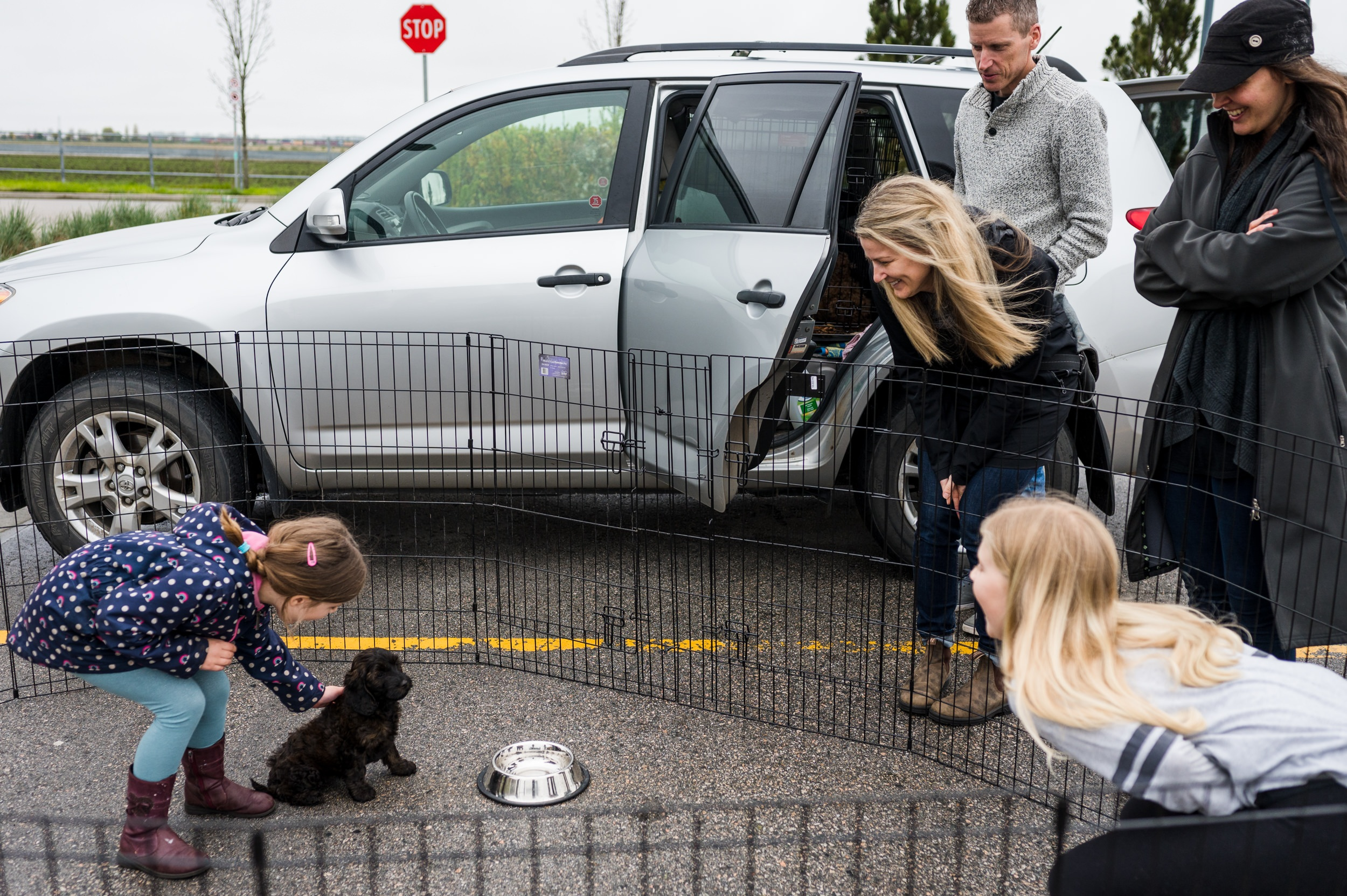 family meeting their puppy for the first time in a parking lot
