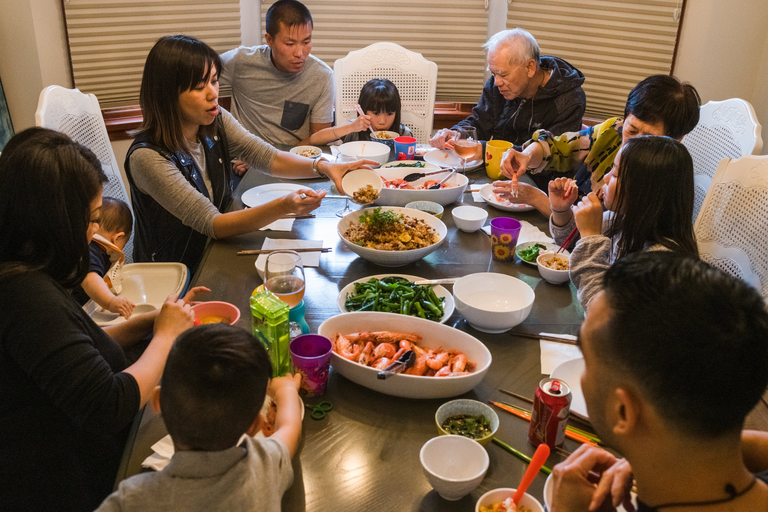 It is spot prawn season and an extended family gathers around the dining table to share a Chinese meal between grandparents, parents, and grandchildren.