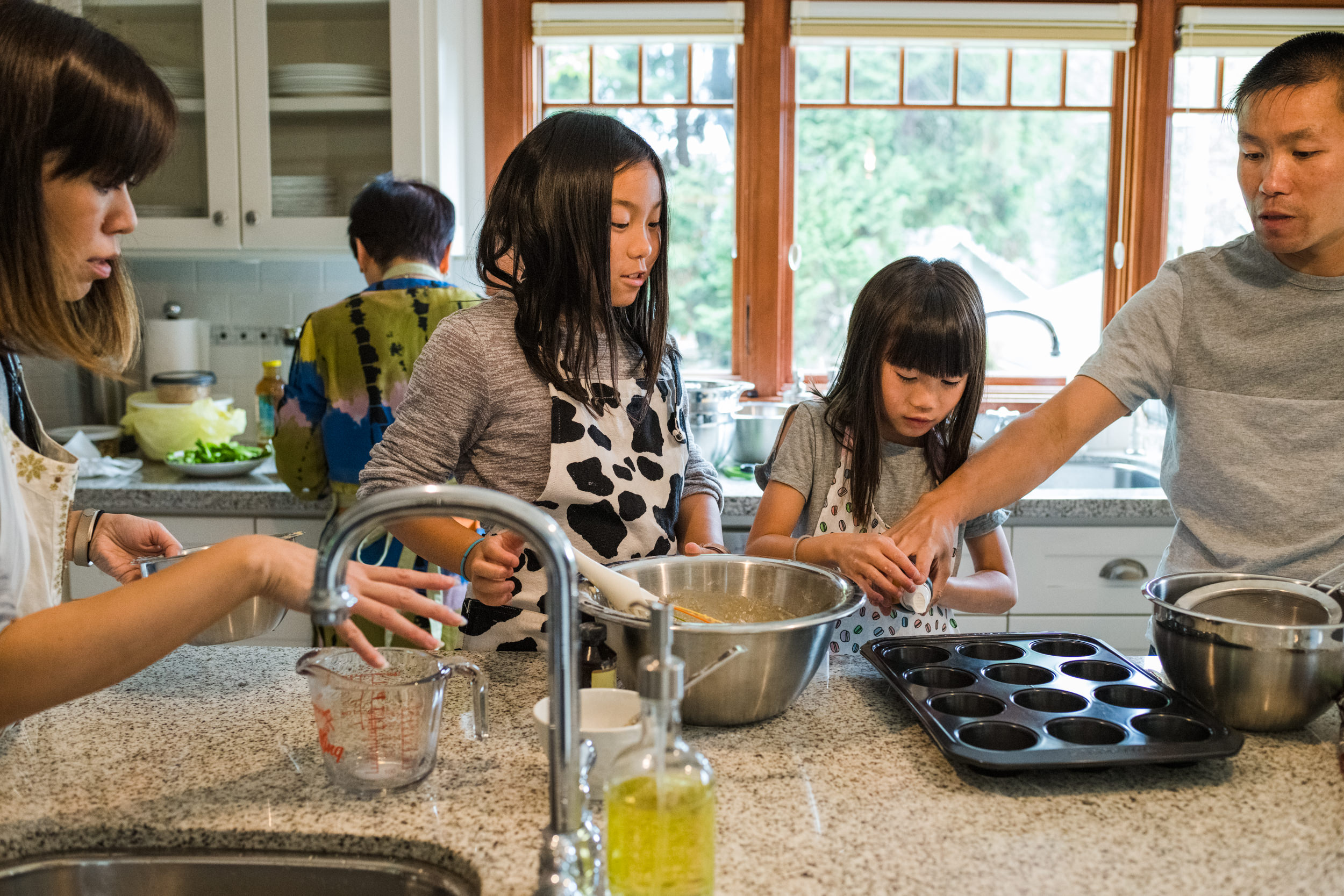 Parents guiding their daughters with baking muffins at the kitchen island.