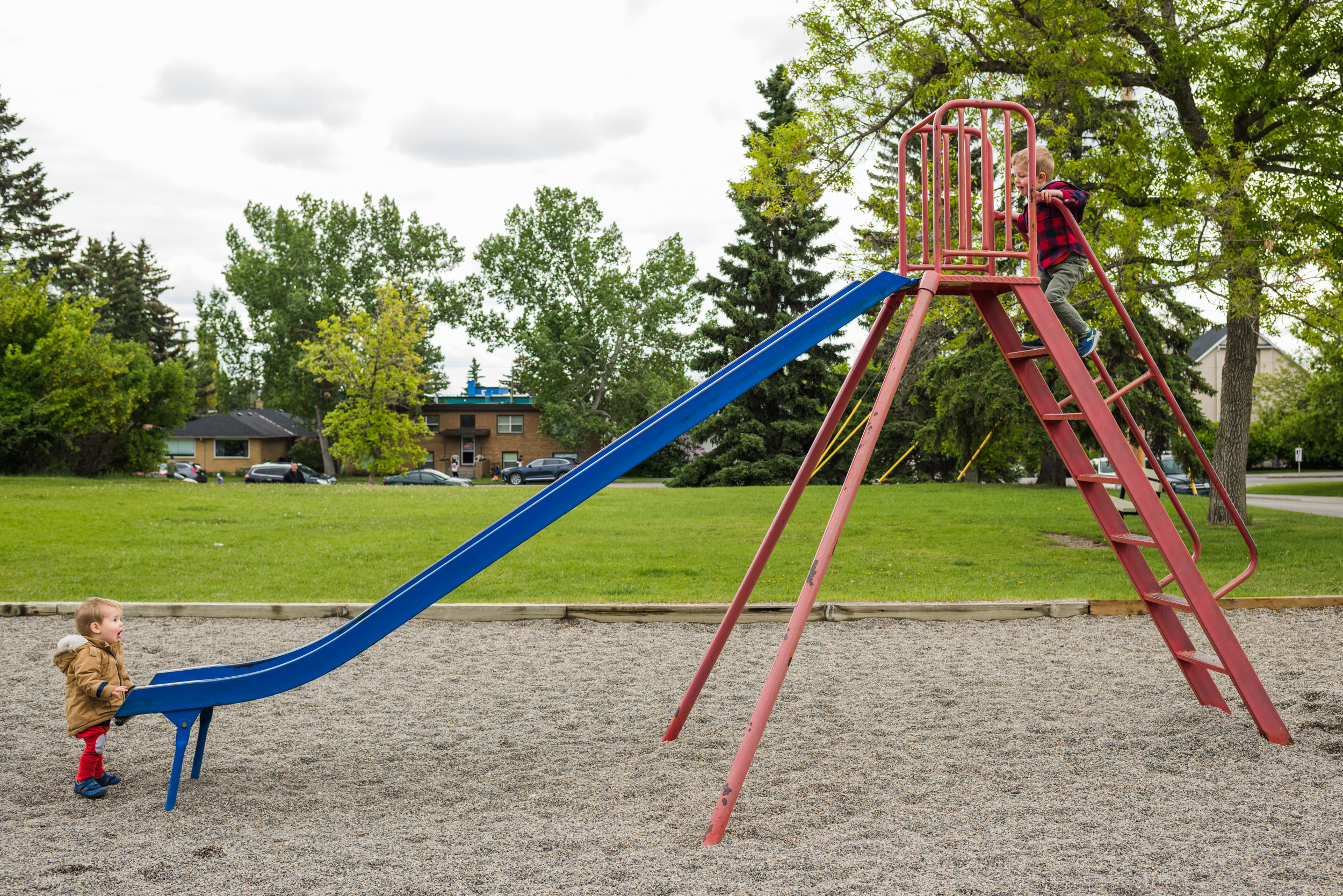 Toddler younger brother waits at the bottom of a slide as his big brother climbs to the top of it at the playground.