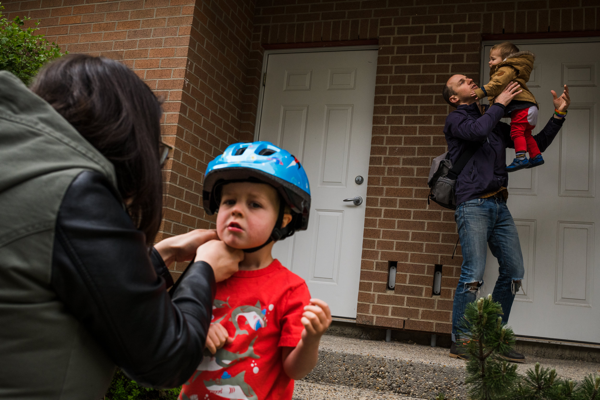 Parents help their two sons get ready for bike riding and a walk outside.
