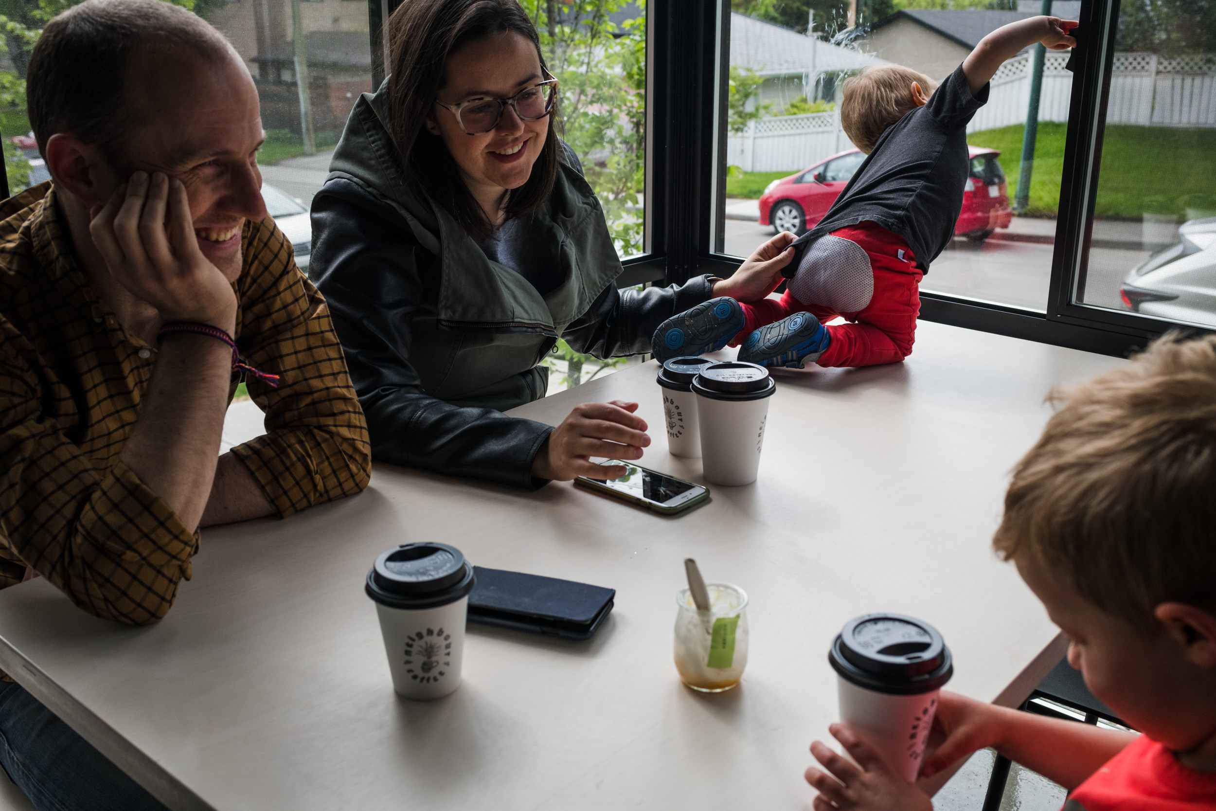 Parents enjoying a coffee with their older son while keeping a hand on their toddler climbing the table and opening a window.