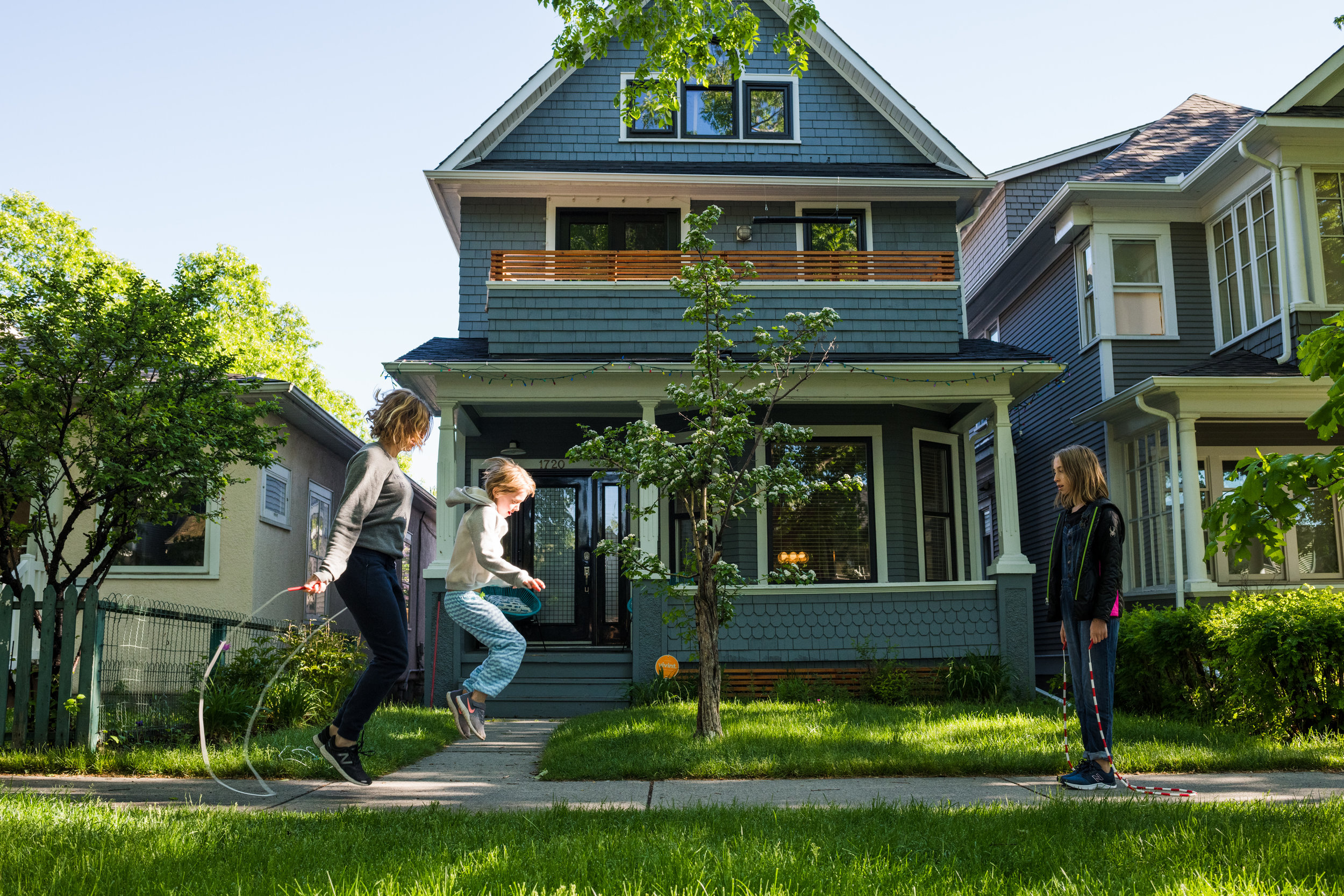 Mother skipping rope with daughters on the sidewalk in front of their home in Calgary.