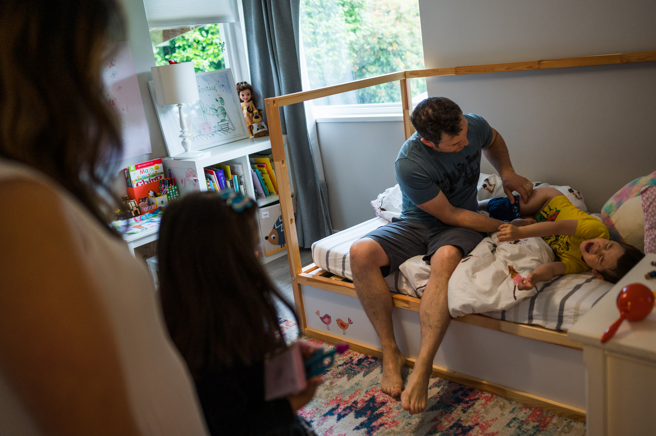 dad tries to dress his son while he is wriggling on his big sister's bed.