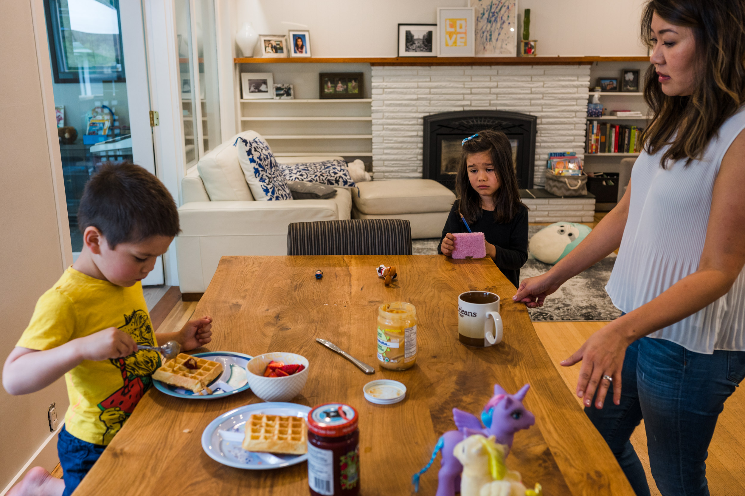 Mom watching her son scooping a lot of peanut butter onto his waffle while his sister appears upset.