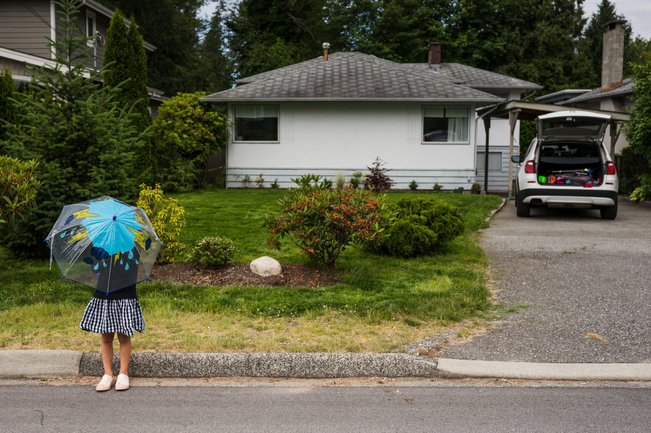 A little girl stands outside in front of her house on a sunny day with a rain umbrella.