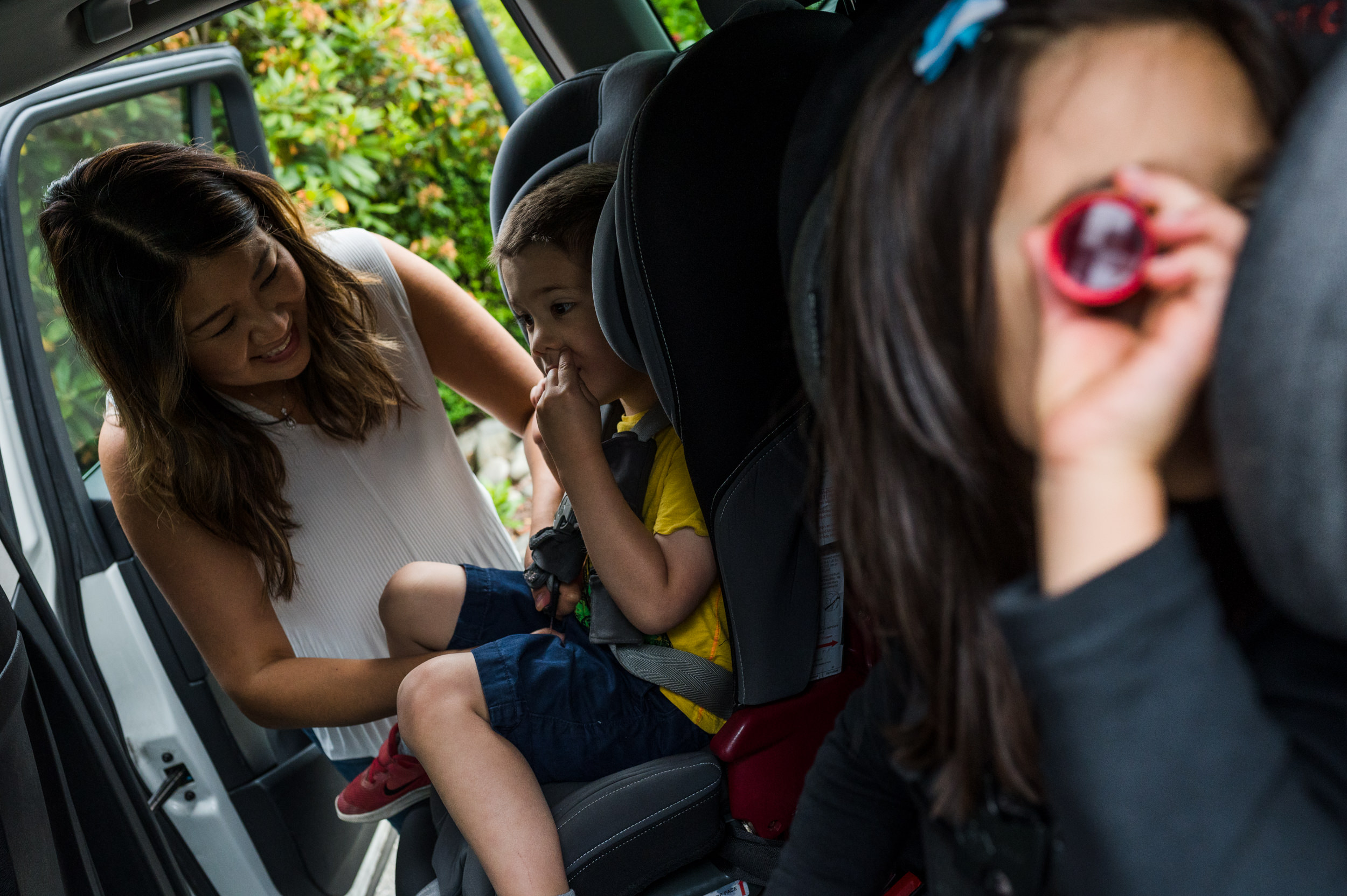 A mother buckles in her son into his carseat while his sister looks out the window with a toy kaleidoscope.