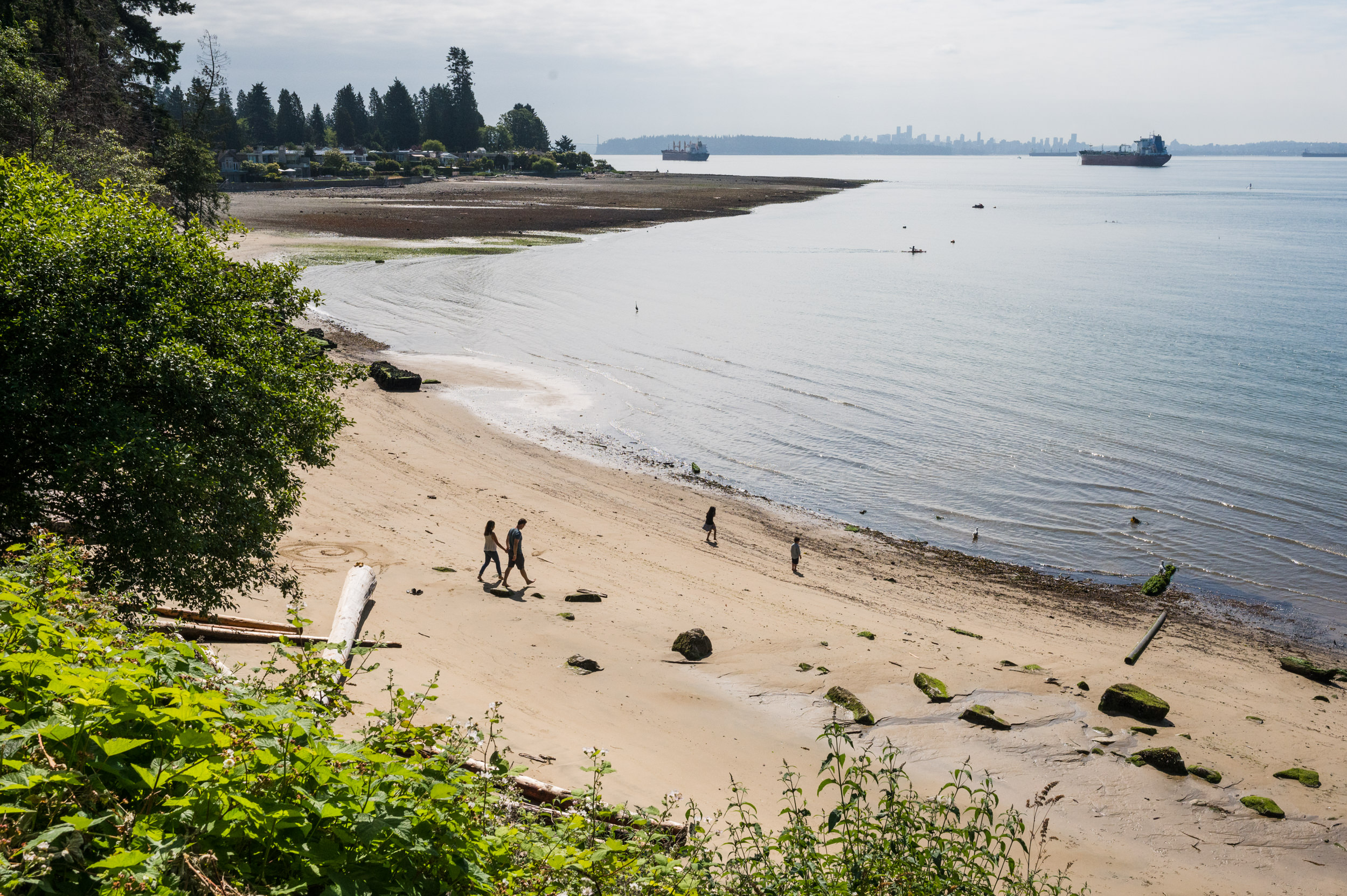 A family explores the sandy shores of a West Vancouver beach at low tide.