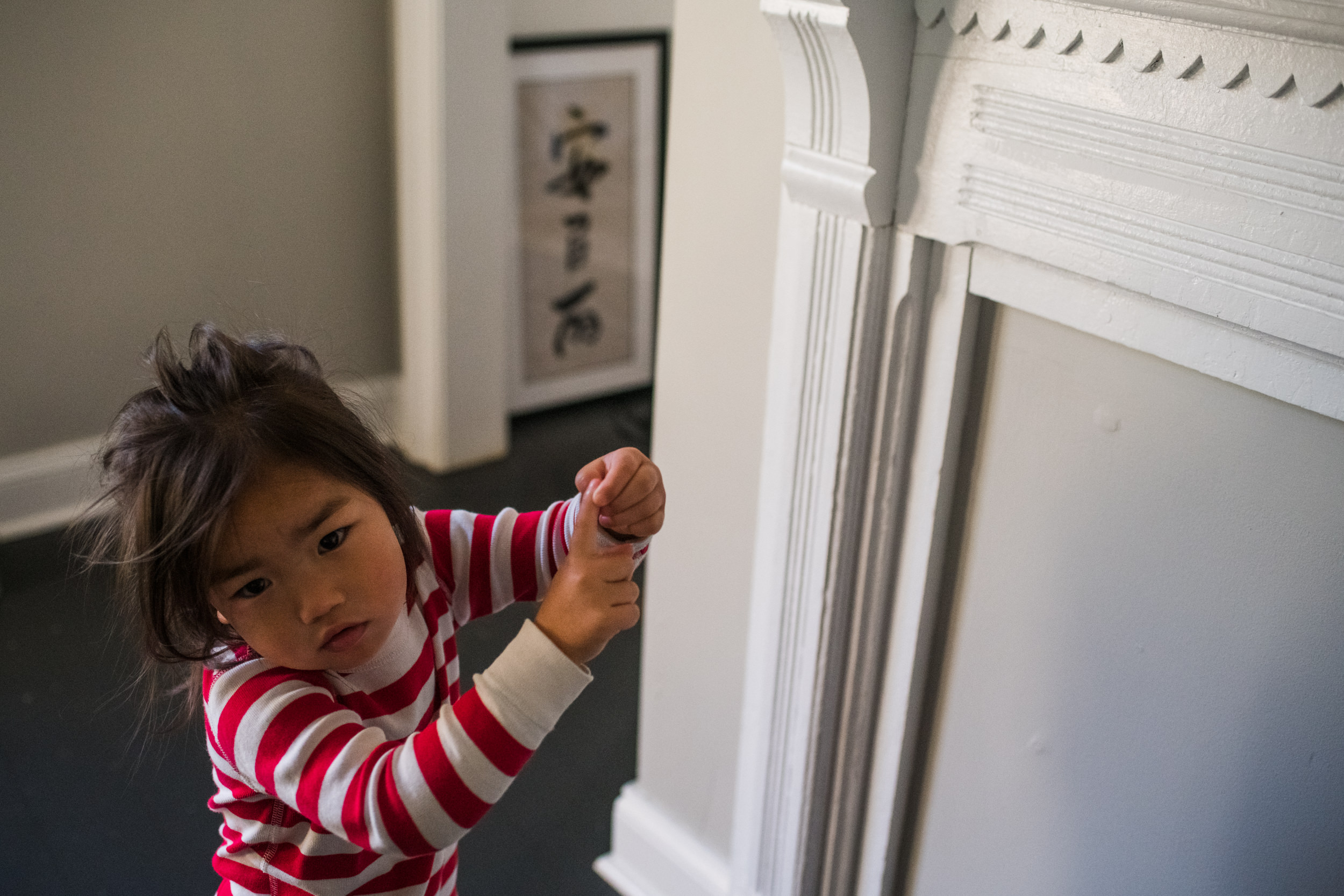 Young girl in the living room with a brush painting of her Chinese name on the wall.