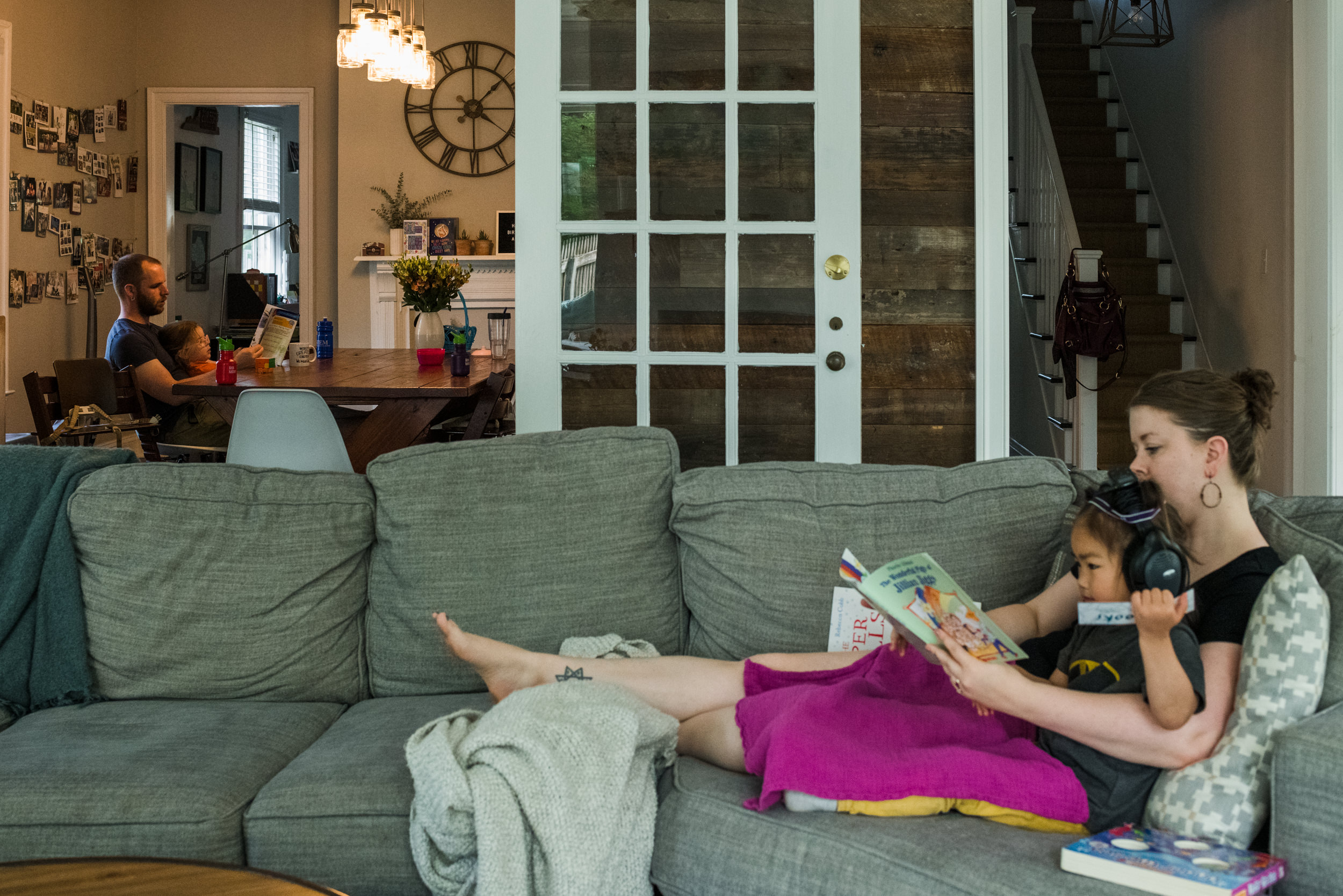 mom and daughter reading together on the couch while dad and other daughter reads together at the dining table.