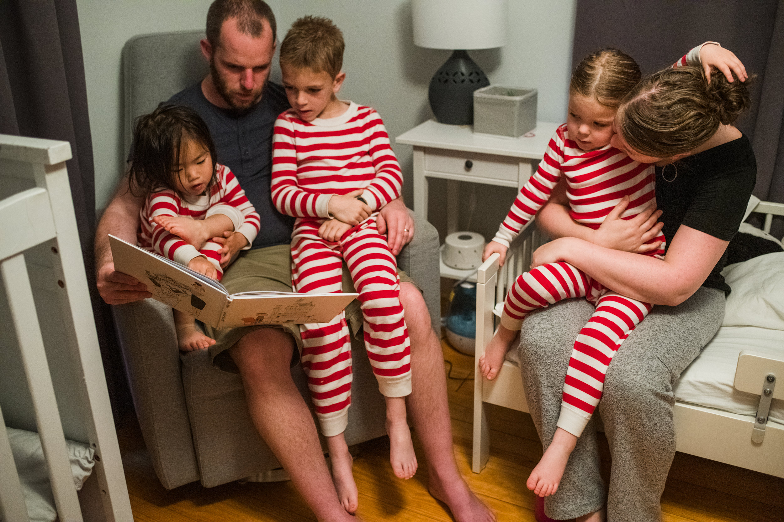 Parents are cuddling with their three children while reading books before bed.