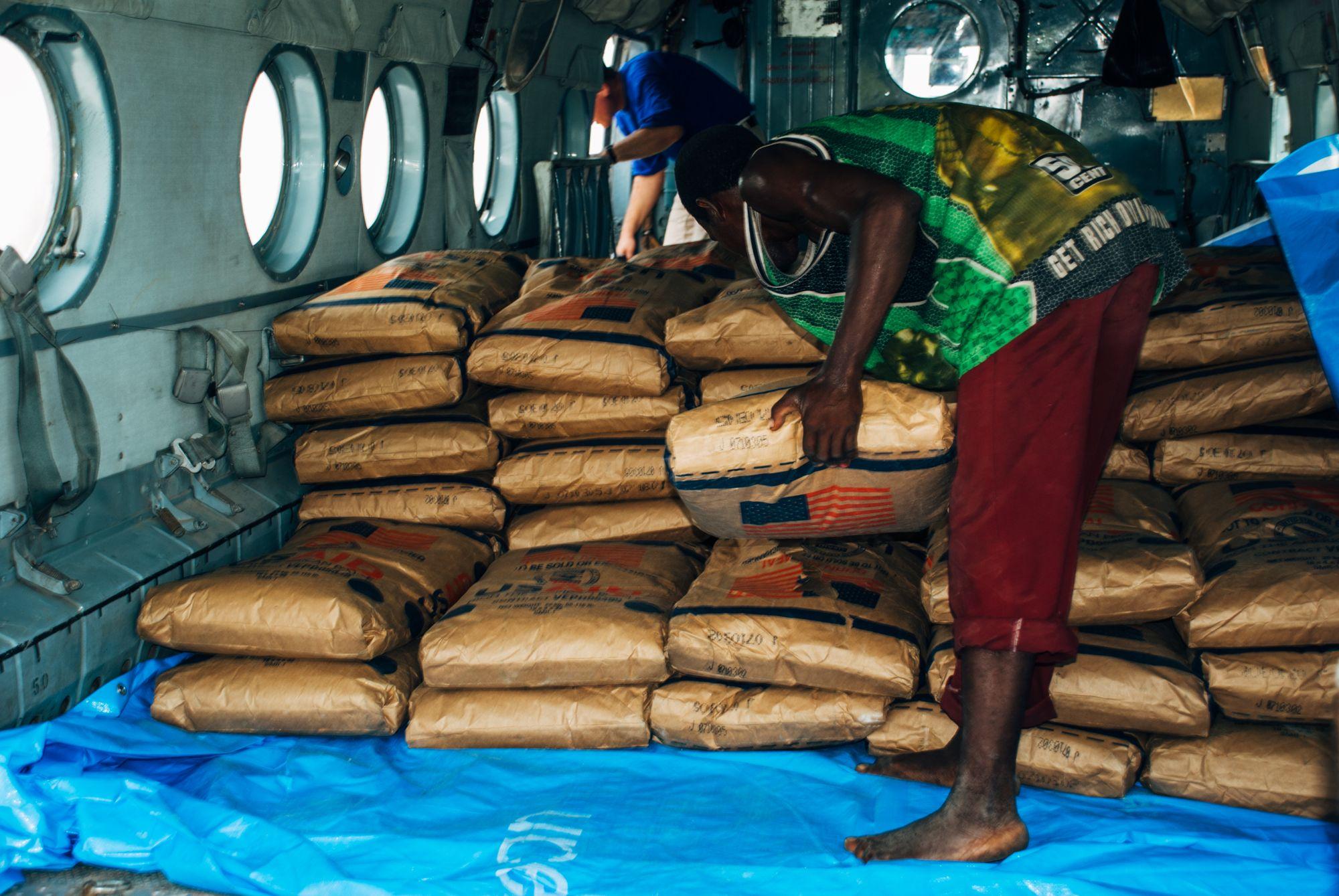 WFP - Flyet for matdrop ankom fra Kongo. Her lesser de på sekker med masimel og ris for å få det ut til steder hvor vannmassene gjør det umulig å komme til
