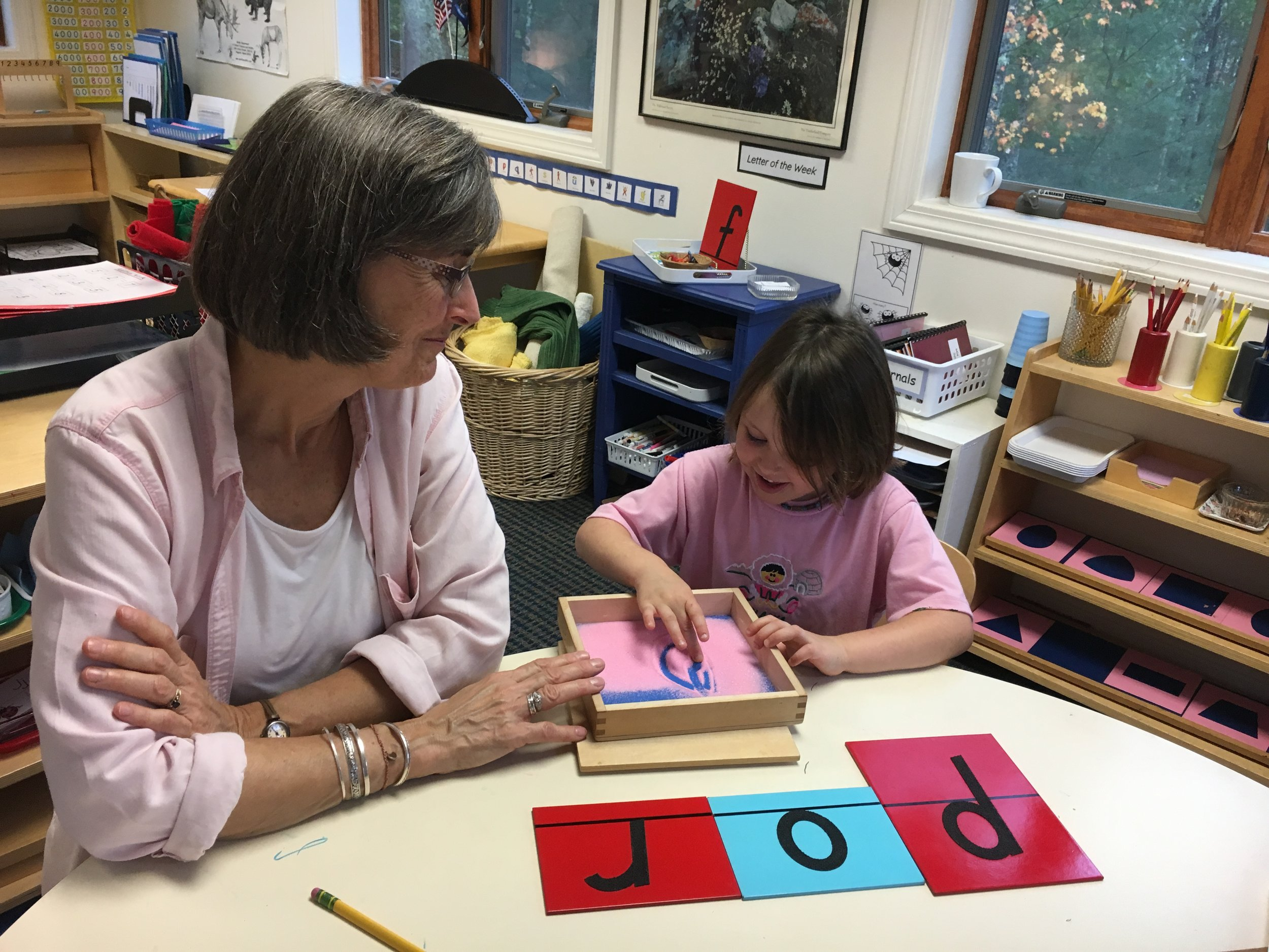This child is receiving a lesson using the sand paper letters.  The lesson  unites the letter's sound with the muscular and visual memory of the letter to prepare the child for writing and reading.