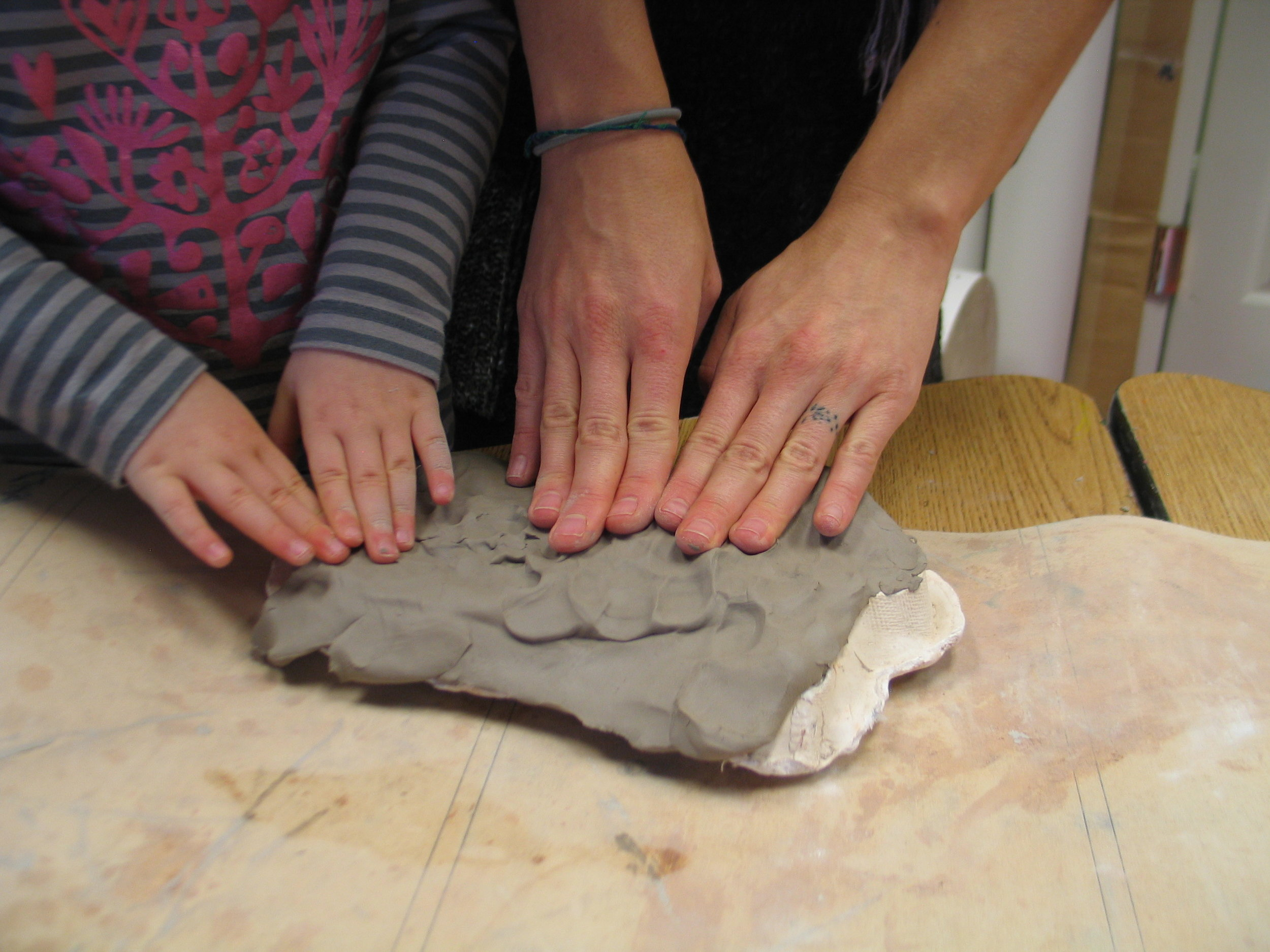 This teacher and student work together to press the clay onto a template.