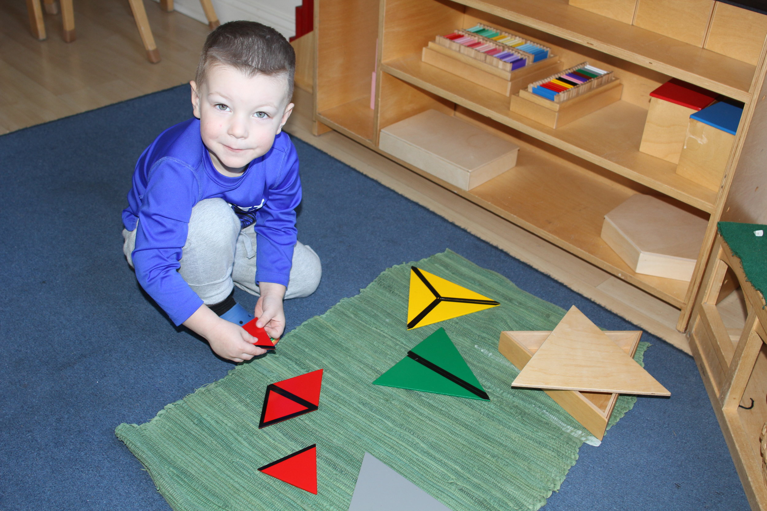 This 3 year old boy works with the triangle box.  The triangle box is a sensorial material that shows that the equilateral triangle can be subdivided into other types of triangles and gives him practical experience in plane geometry.