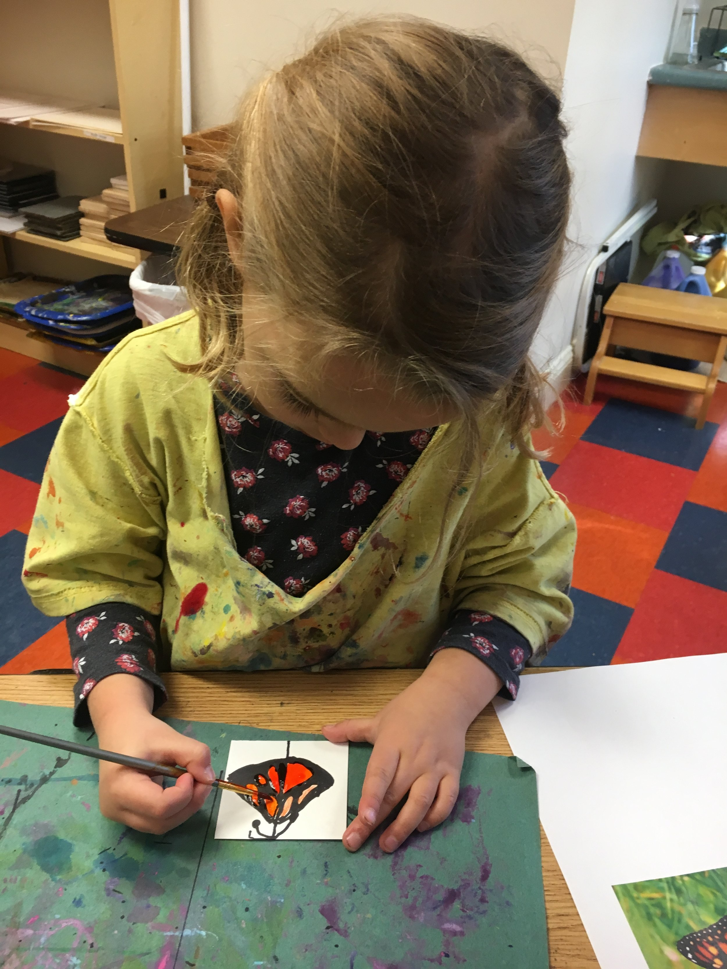 This 4 year old girl uses black sharpie and water color paints to create a Monarch butterfly in the art studio.
