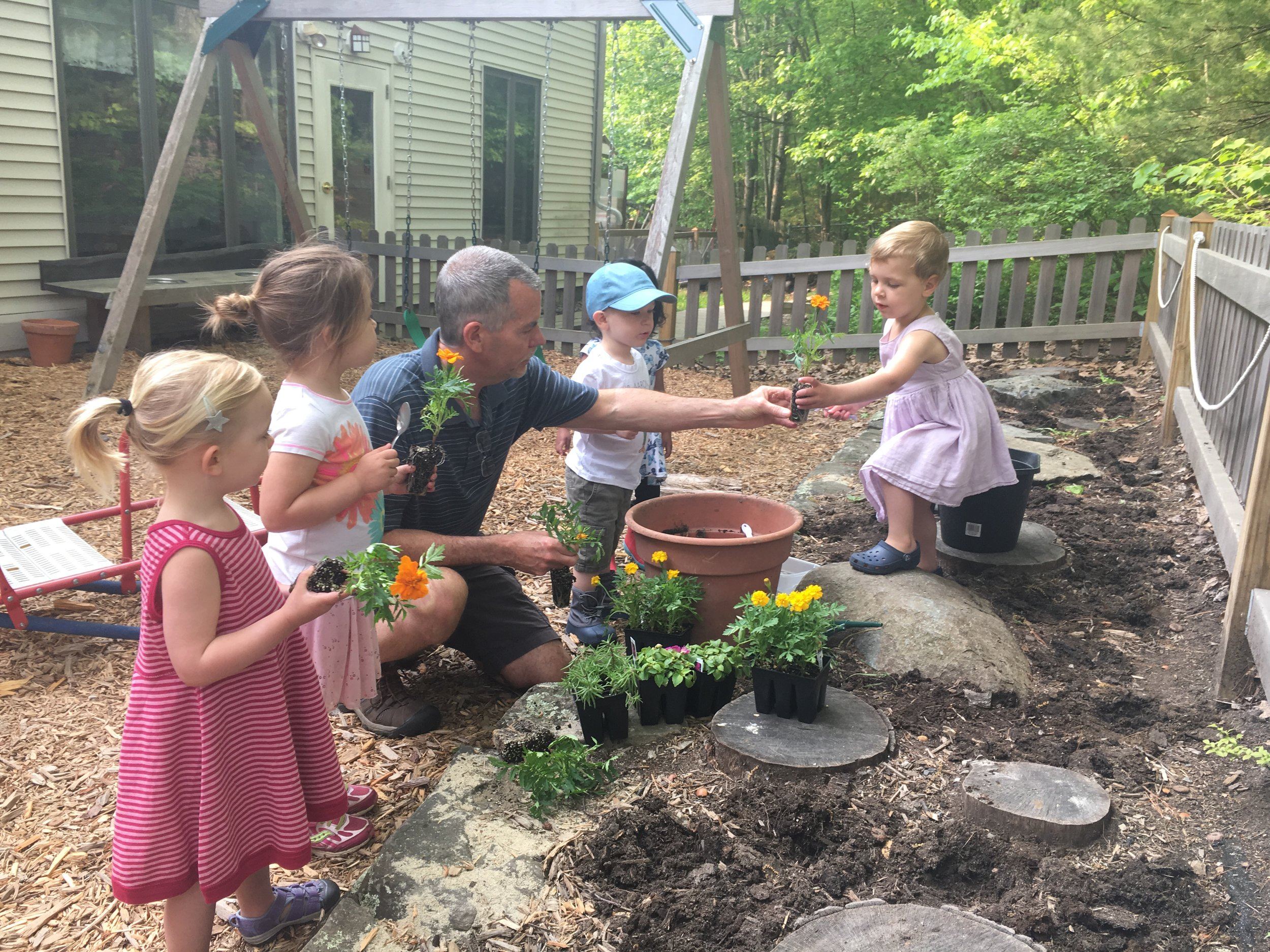 Planting flowers in the toddler playground garden with Michael.