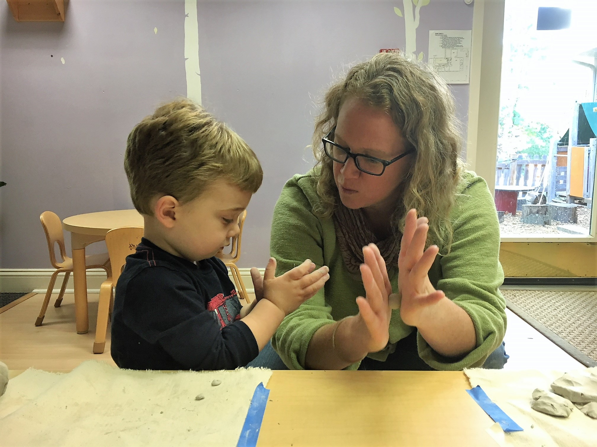 Studio art teacher, Sarah, shows this toddler how to make a ball with clay.