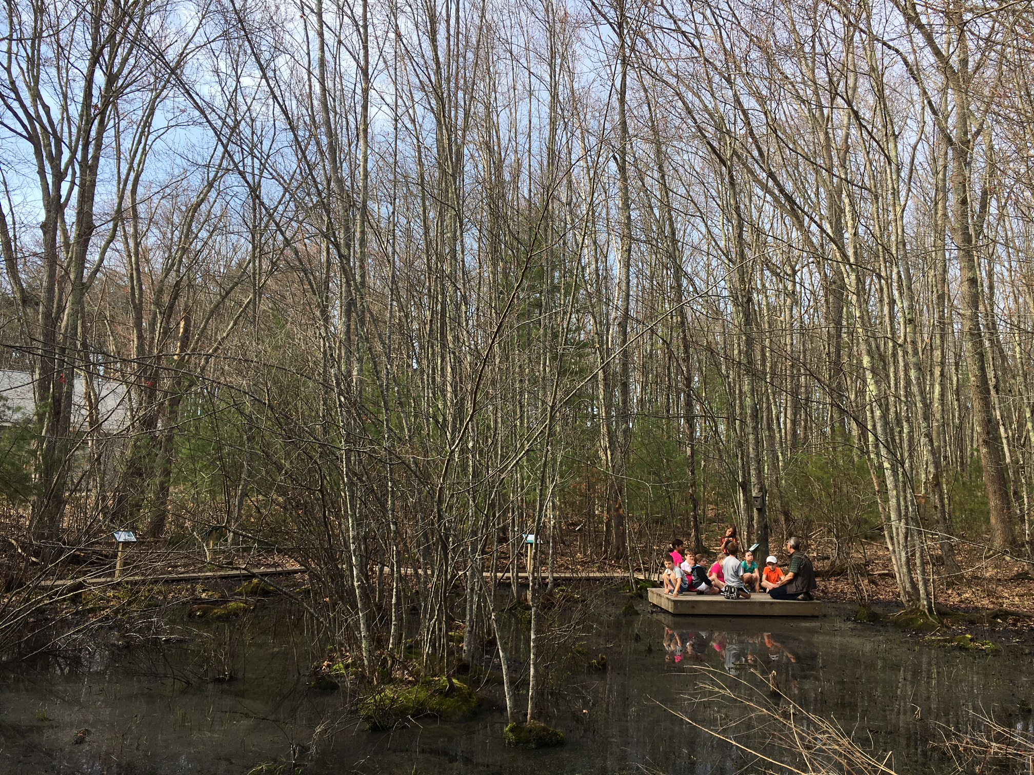 The lower elementary class takes a lesson out to the vernal pool.