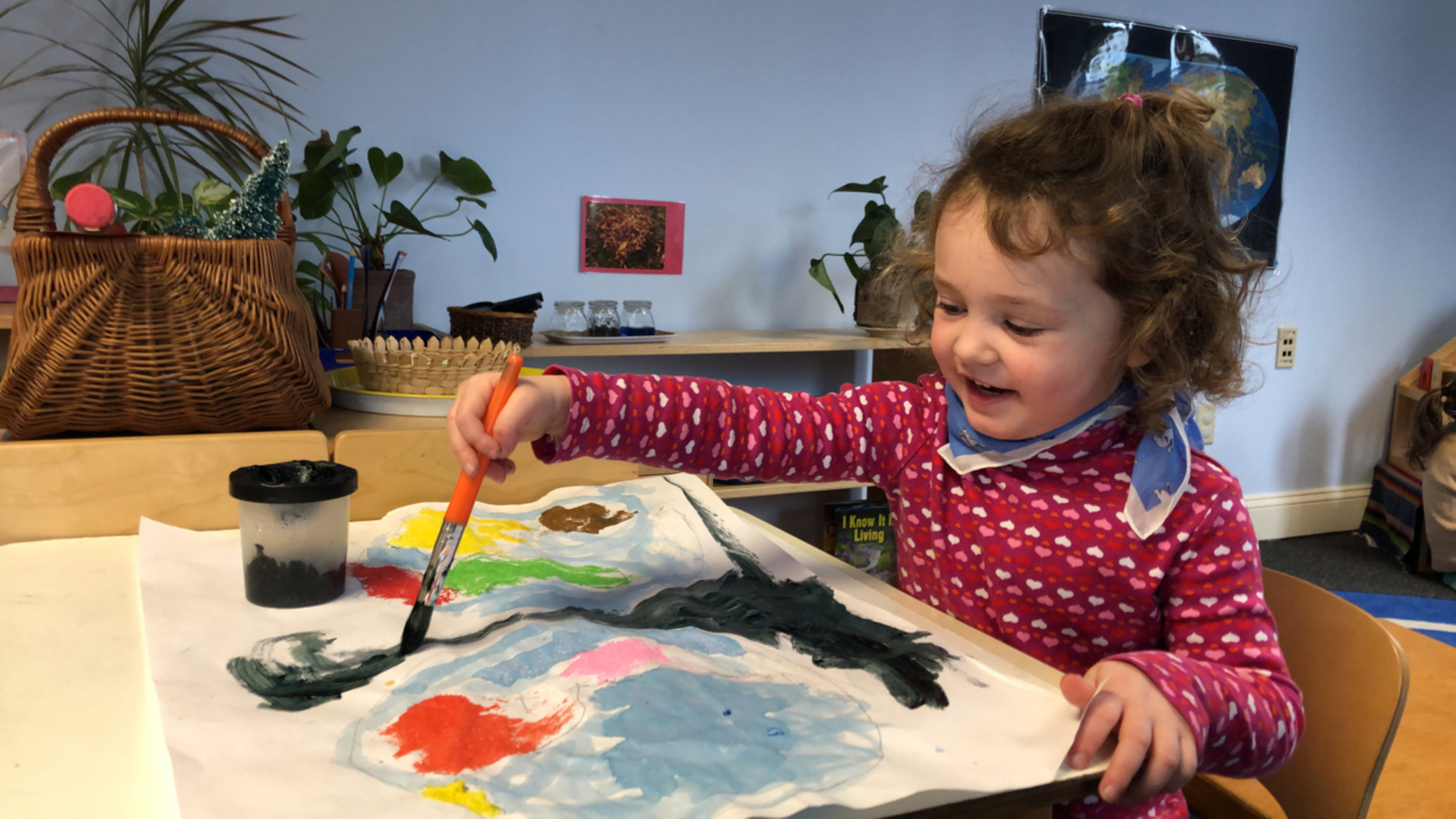 This four year old girl paints the outer space area of her continent map.