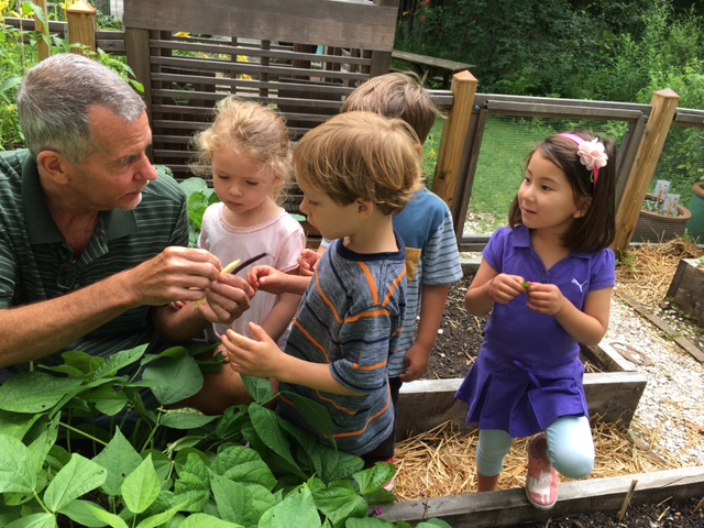 These 3-6 students enjoy the fruits of our school garden with garden program coordinator, Michael.