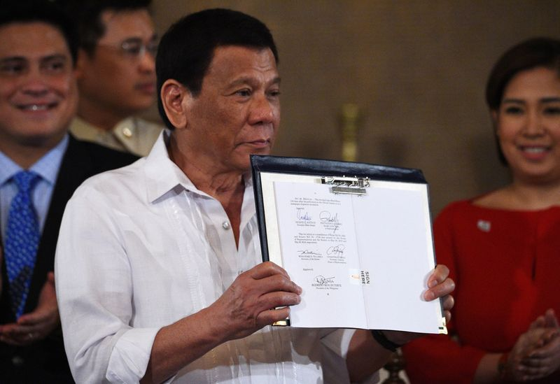 President Rodrigo Duterte presents signed Identification System Act.  Accessed Nov 06, 2018. Source: Ted Aljibe/AFP/Getty Images.