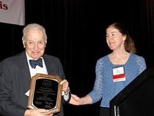 Nobel laureate Dr. Ken Arrow receives the 2009 Distinguished Achievement Award from then SRA President Dr. Alison Cullen.