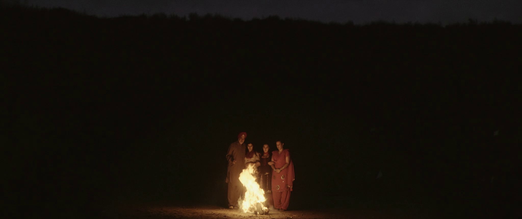 three personne around a fire in the desert