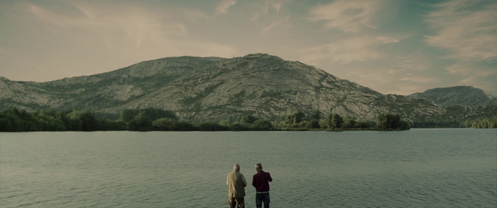 beautiful view with two men contemplating the mountain lined with a lake