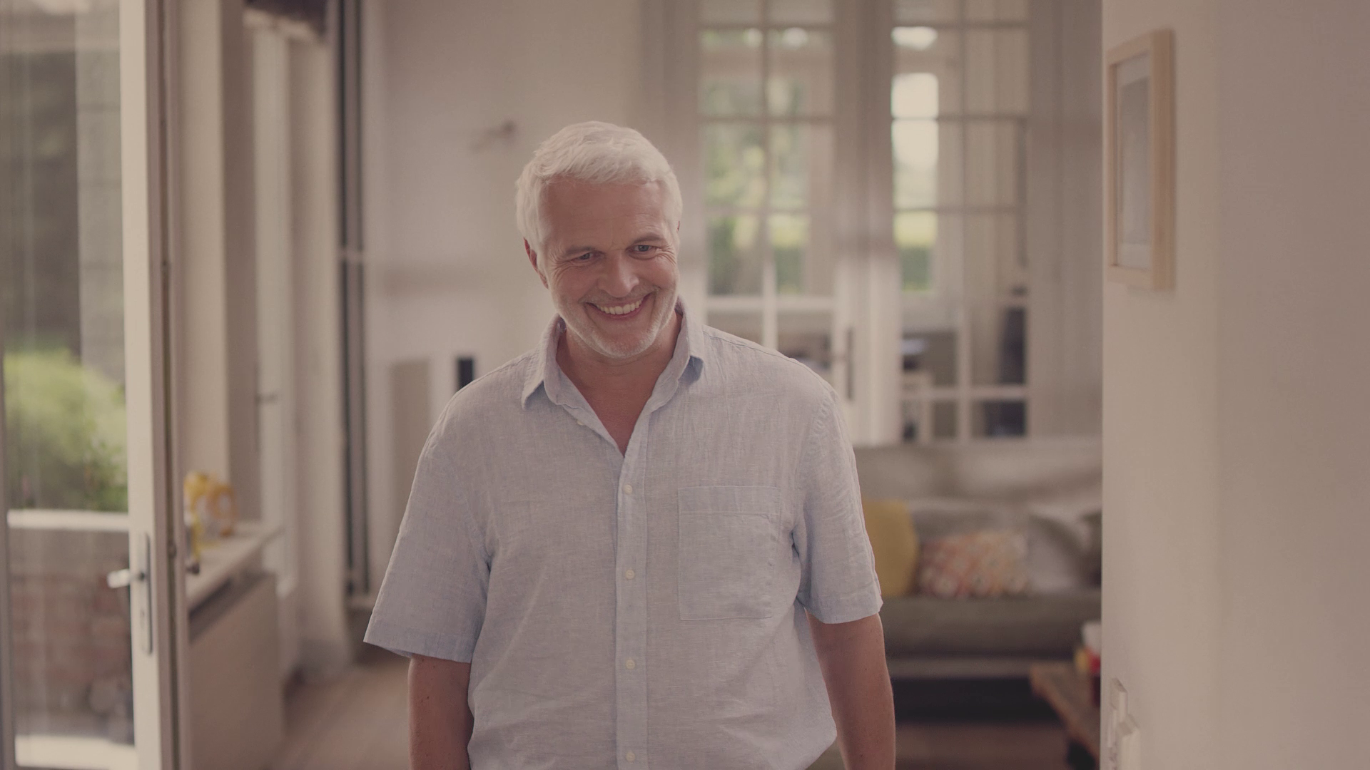 old smiling man with white hair walking in the kitchen